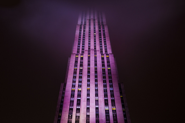 [Image description: photograph of a skyscraper at night, taken from beneath. The pink building stands in the centre of the image, reaching up into the clouds above, with darkness on either side.]   Dave Doe  / Creative Commons