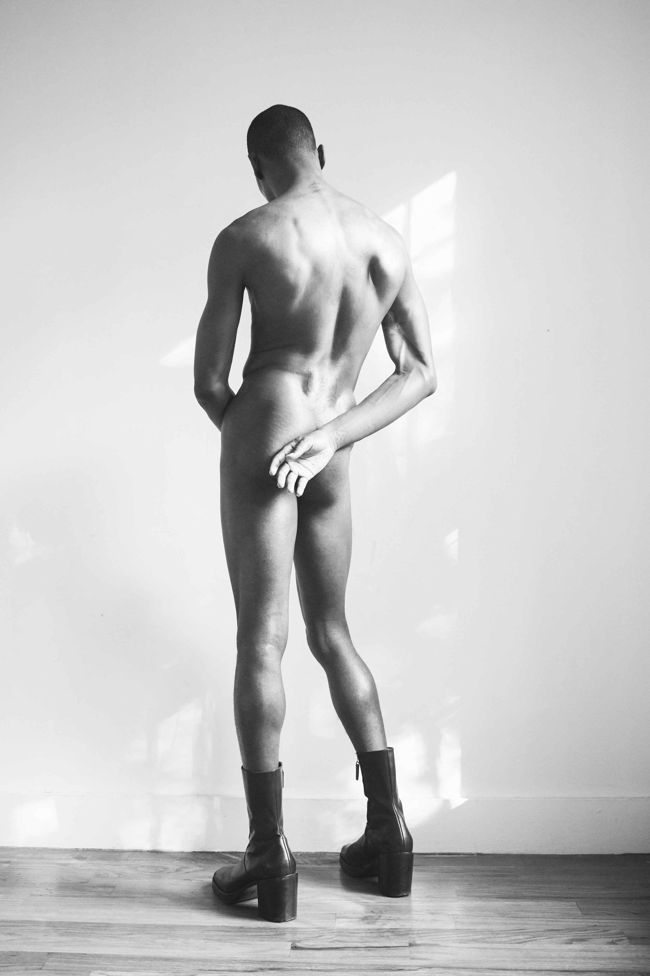 [Image description: photograph of a person standing against a pale wall, with their back to the camera. They are naked, but for a pair of leather boots with thick heels.]