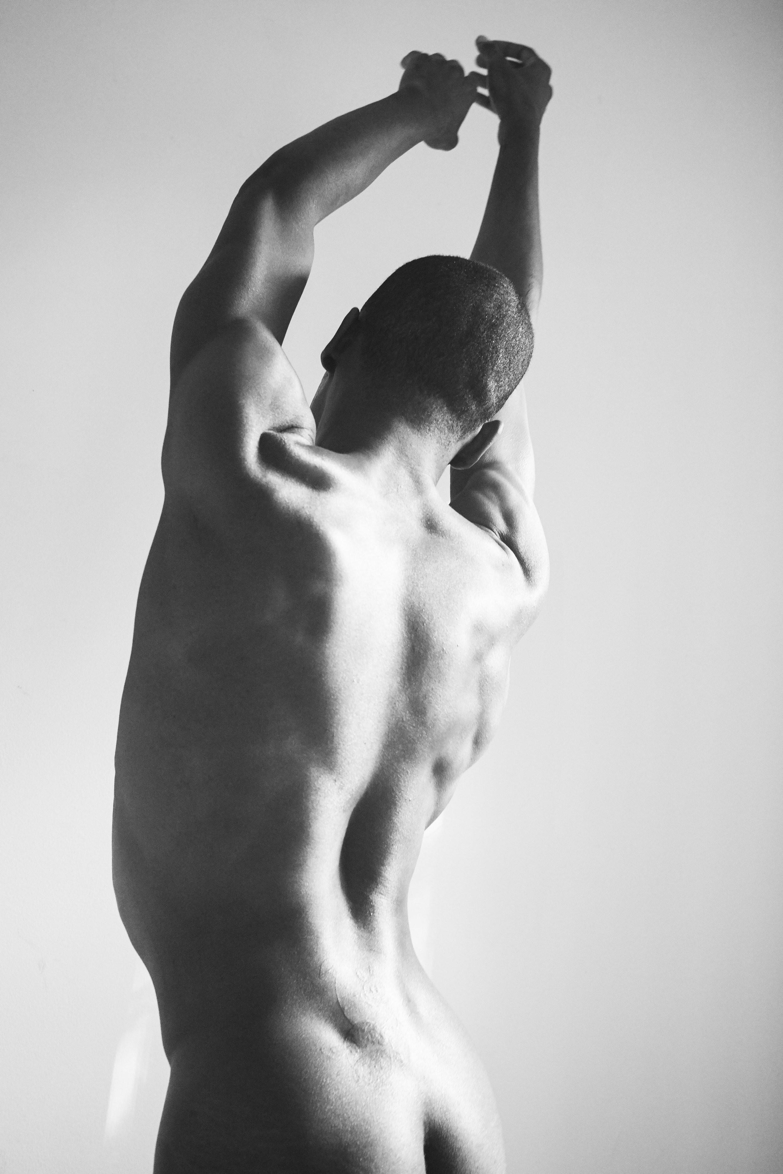 [Image description: photograph of a person standing, naked, against a pale background, with their back toward the camera. Their arms are raised and touching above their head, and they stand in a slight lateral bend toward the upper right corner of the image.]