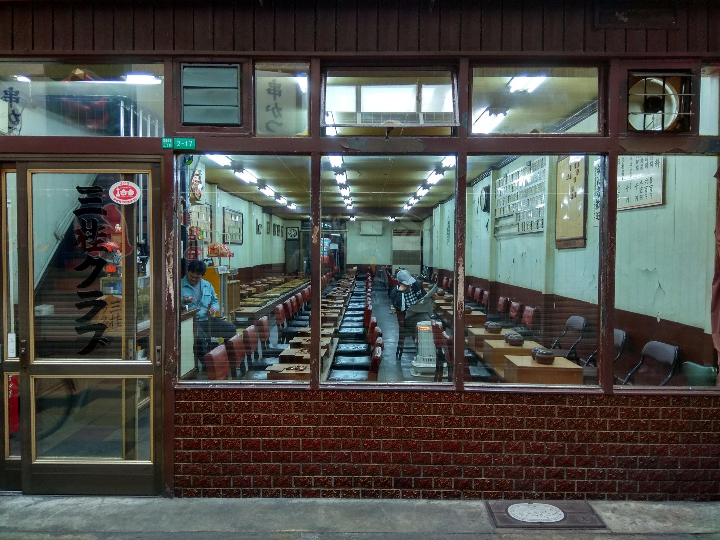 [Image description: photograph of the outside of a Go club. The place is empty, but for a single customer and one worker. Harsh neon strip lighting runs the length of the ceiling.]