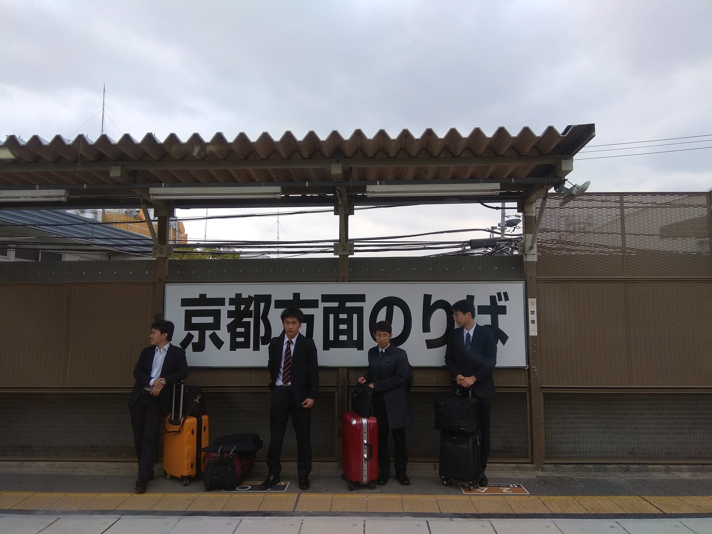 [Image description: photograph of four people dressed in business suits, standing on a train platform. There is a white sign bearing black writing behind them.]