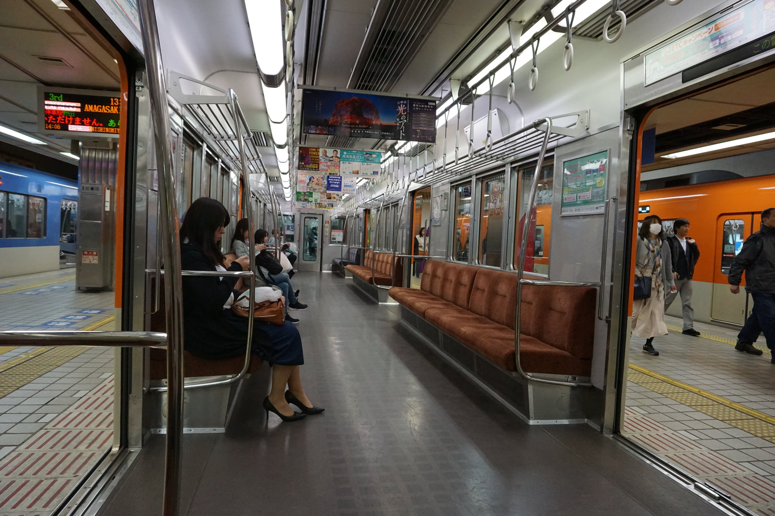 [Image description: photograph of the inside of a train carriage. Only four people are seated inside, all on the left. The doors open onto the platform on both sides of the train. One or two people are walking past the train to the right.]