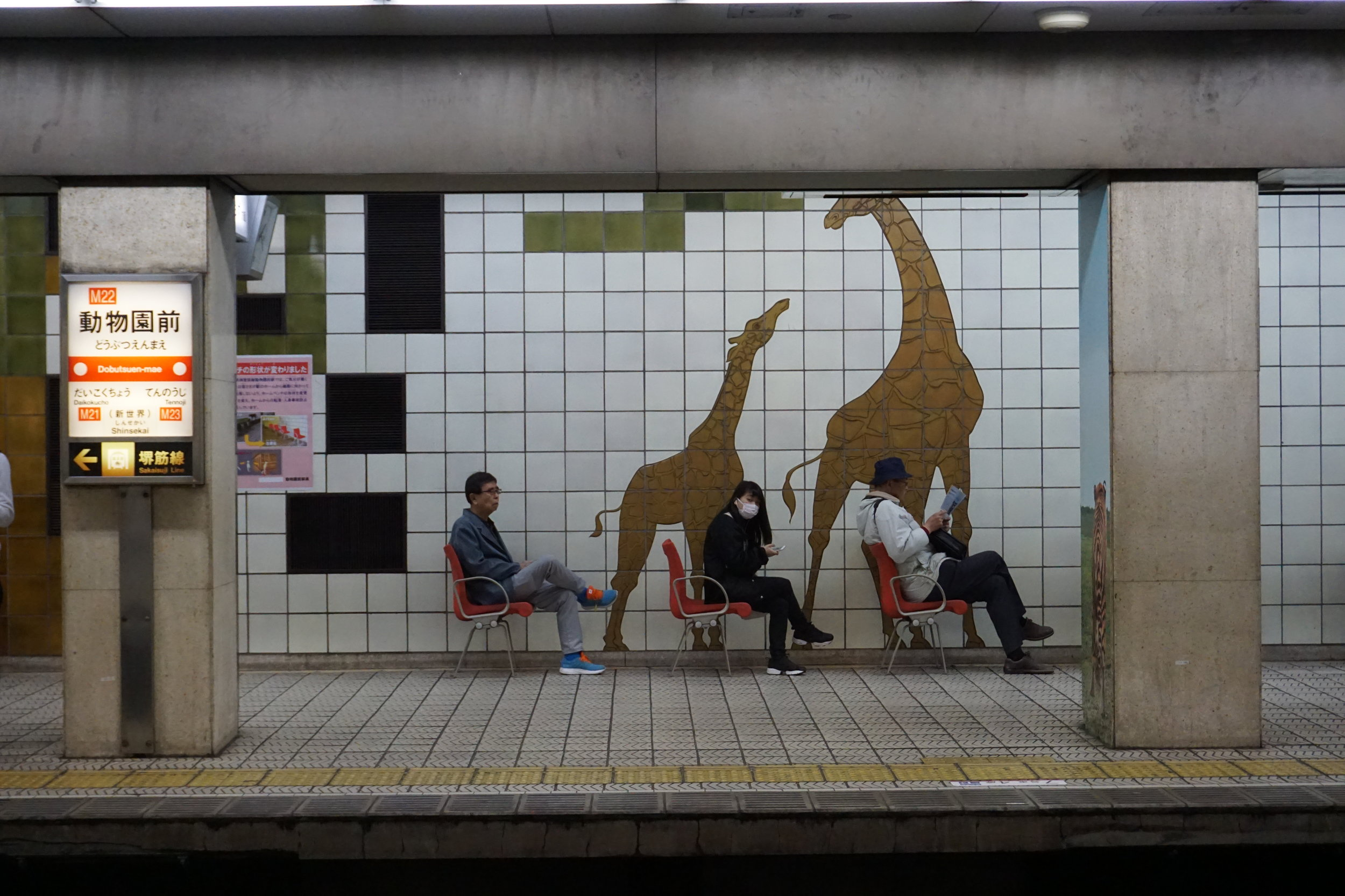 [Image description: photograph of three people sitting in chairs on a train platform. On the wall behind them is a mural of two giraffes.]