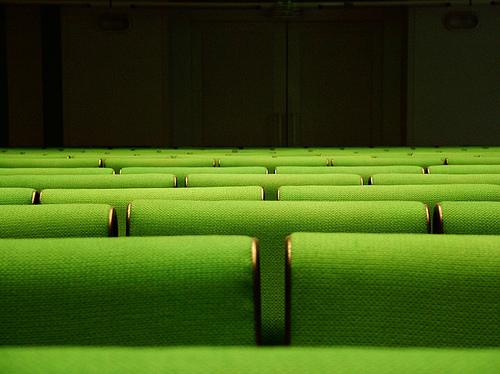 [Image description: close photograph of rows of seating in a lecture hall. A set of double doors is visible in the background.]  Dimitris Kalogeropoylos / Creative Commons