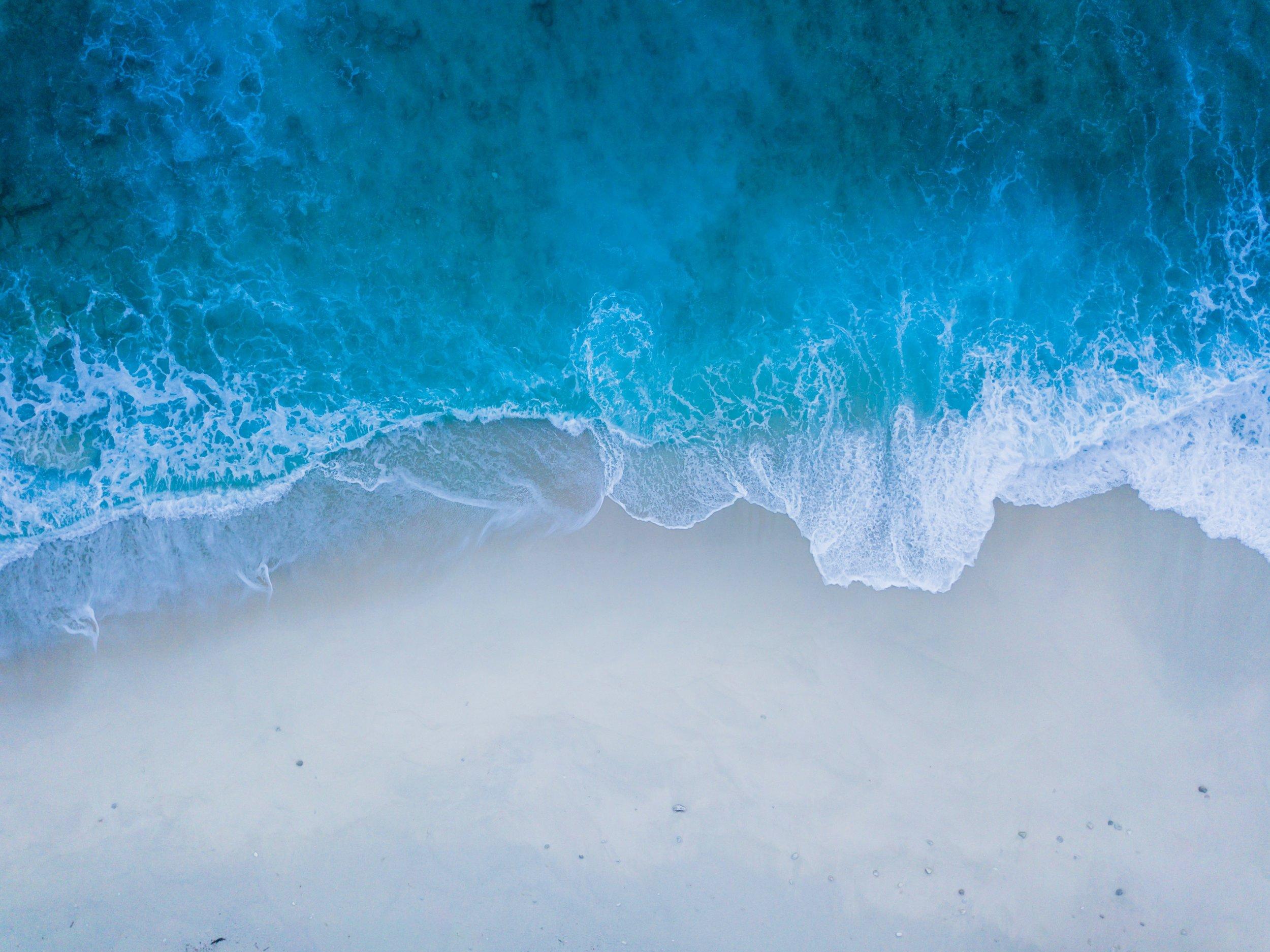 Photo by  Nattu Adnan on  Unsplash    [Image Description: an aerial photograph of crisp blue waves washing upon a white sand shore]