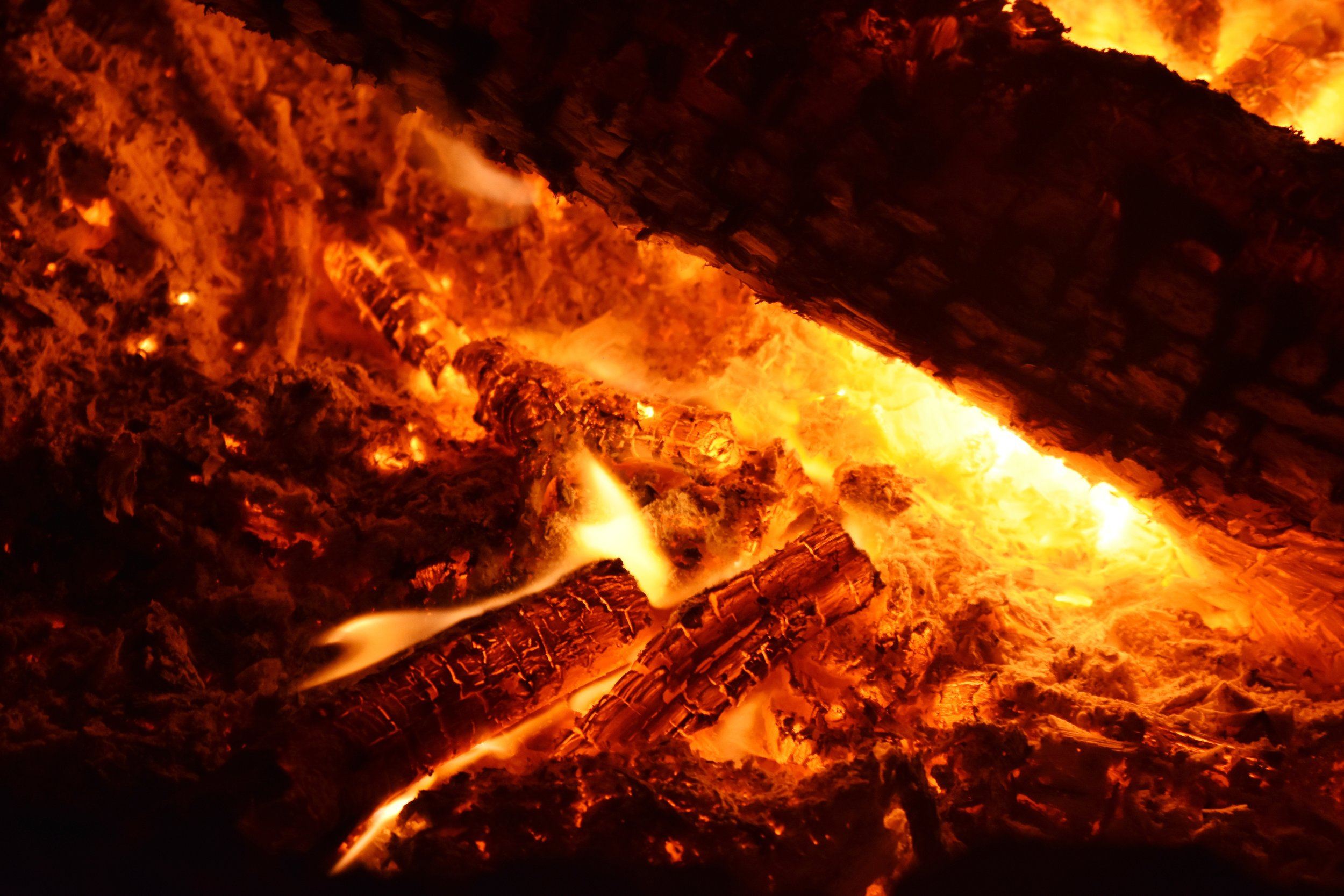Photo by  Drew Farwell on  Unsplash    [Image Description: The smoldering embers of a campfire bloom and brighten around a charred wooden log]