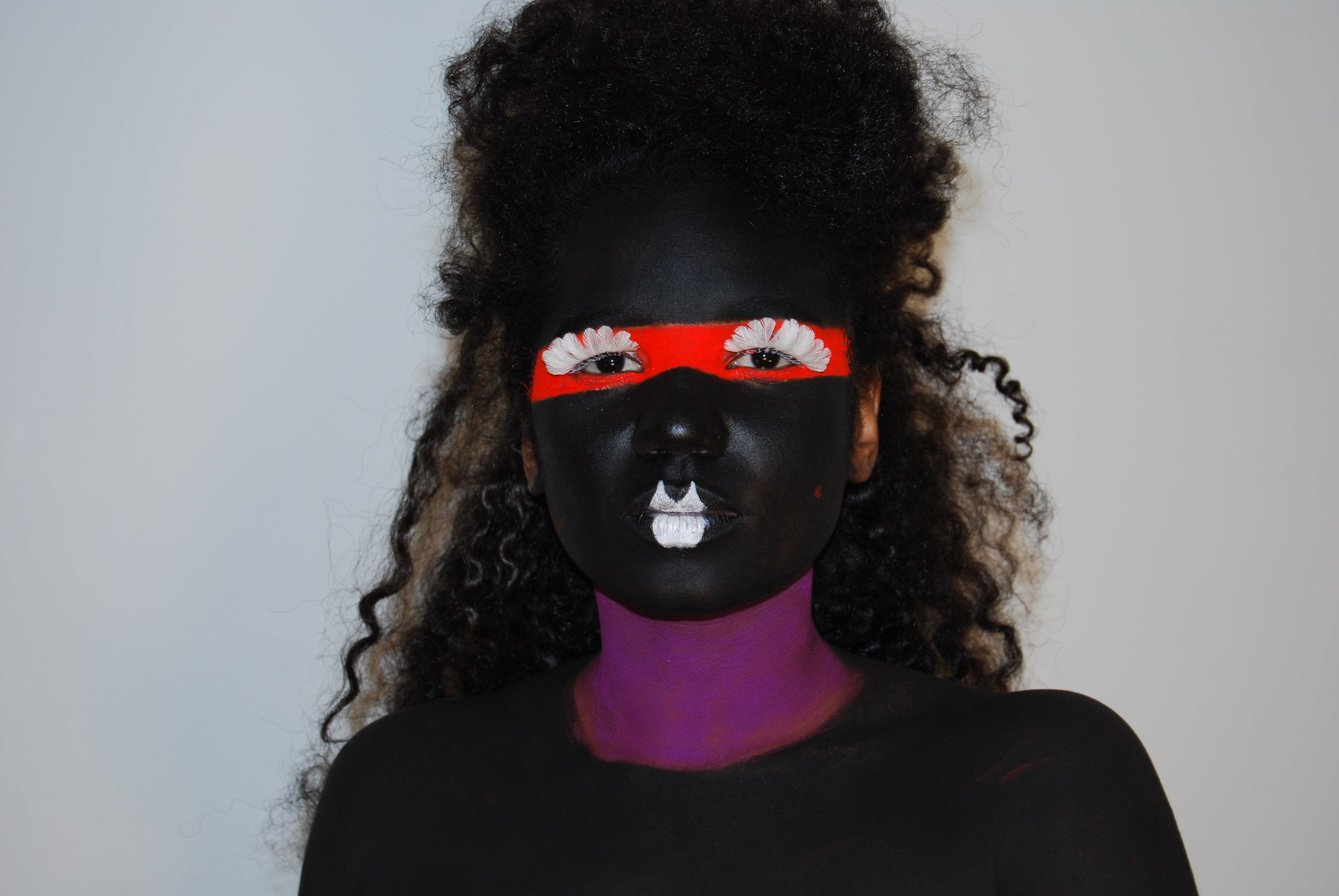"Photo Credit:  Ayesha  ""AYESHA is a rapper and producer with a foundation in hip-hop and dancehall that moves out of the box into experimental electronic music.""   [Image Description: a female bodied person with black face paint, white feathered lashes, and a white painted pout looks directly into the camera. A red strip bands their eyes with their brown hair teased into a beehive.]"