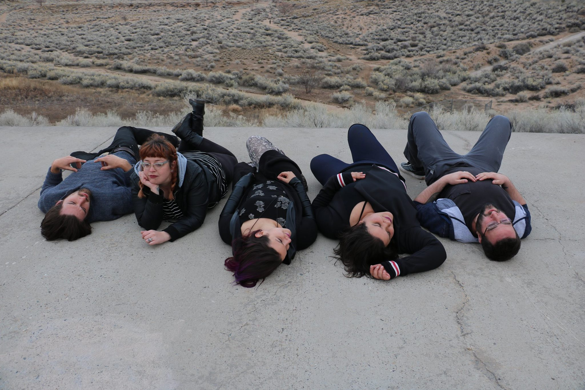 Photo by  Chicharra    [Image Description: Five people lay on their backs on concrete pavement, fanned out in front of a desert landscape.]