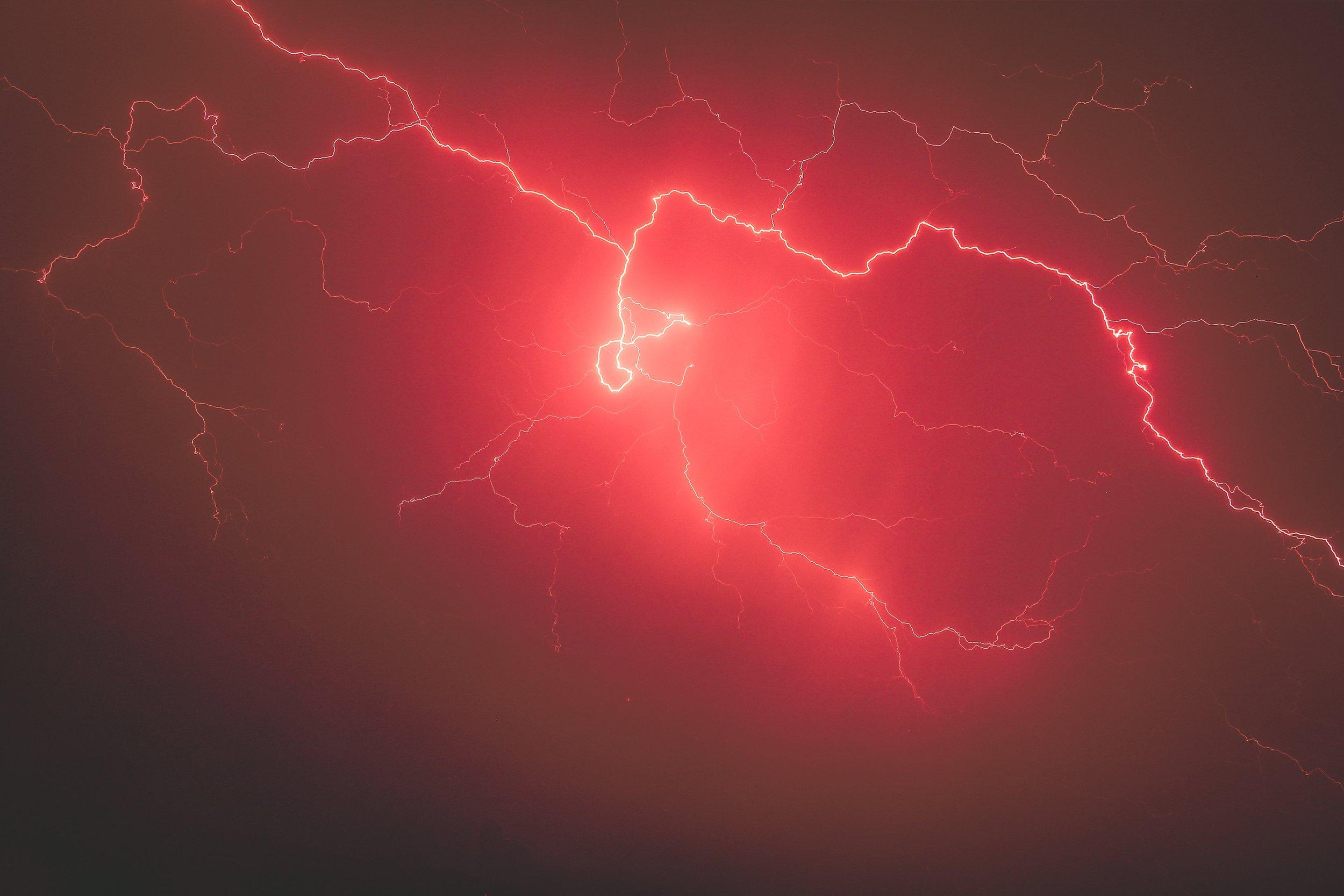 Photo by  Derek Thomson on  Unsplash    [Image Description: Cracks of lightning spread across the sky in a red haze.]