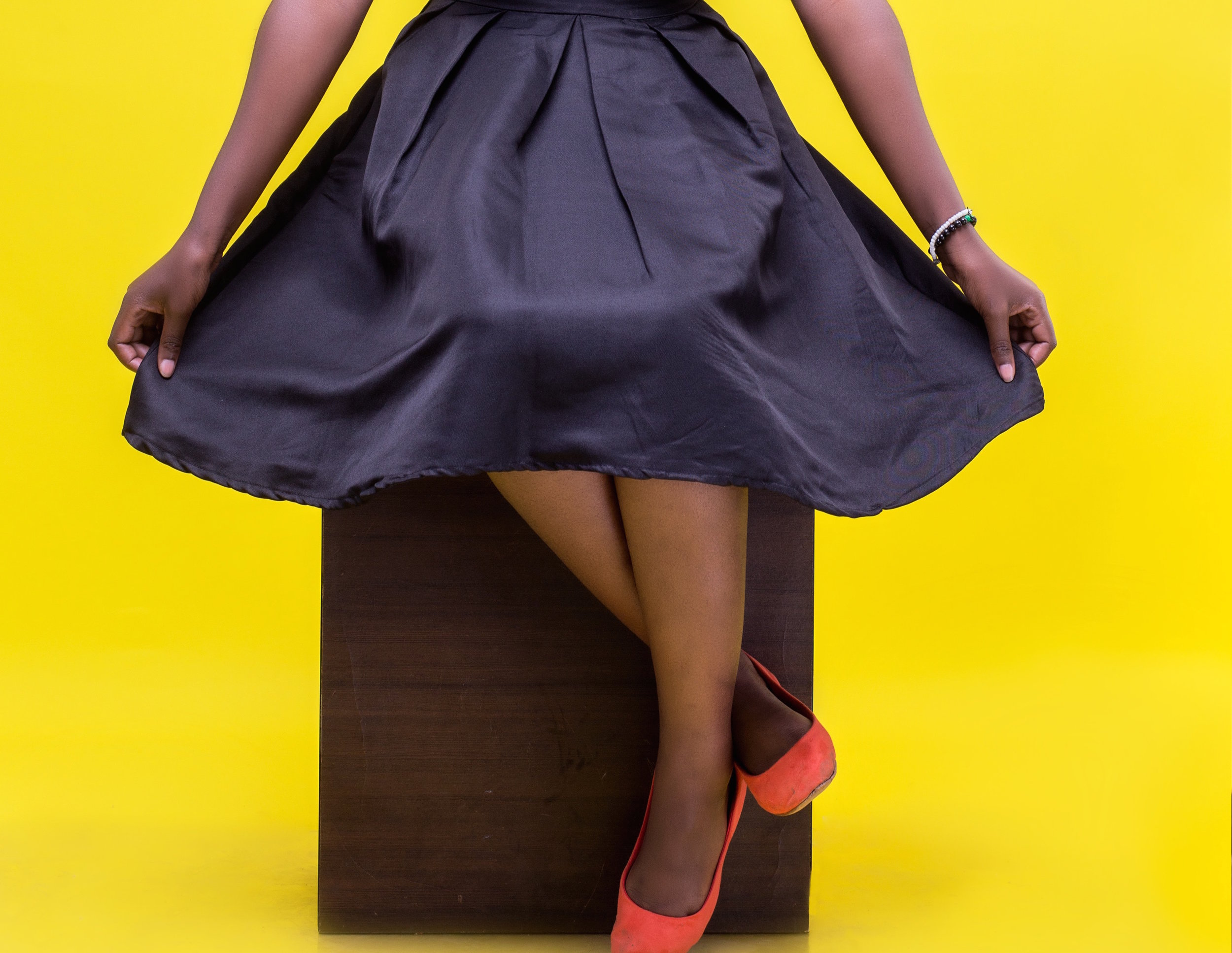 Josepha Mafubo //Creative Commons   [Photo description: a young black womans spreads out her arms and skirt as she sits on a wooden stool].