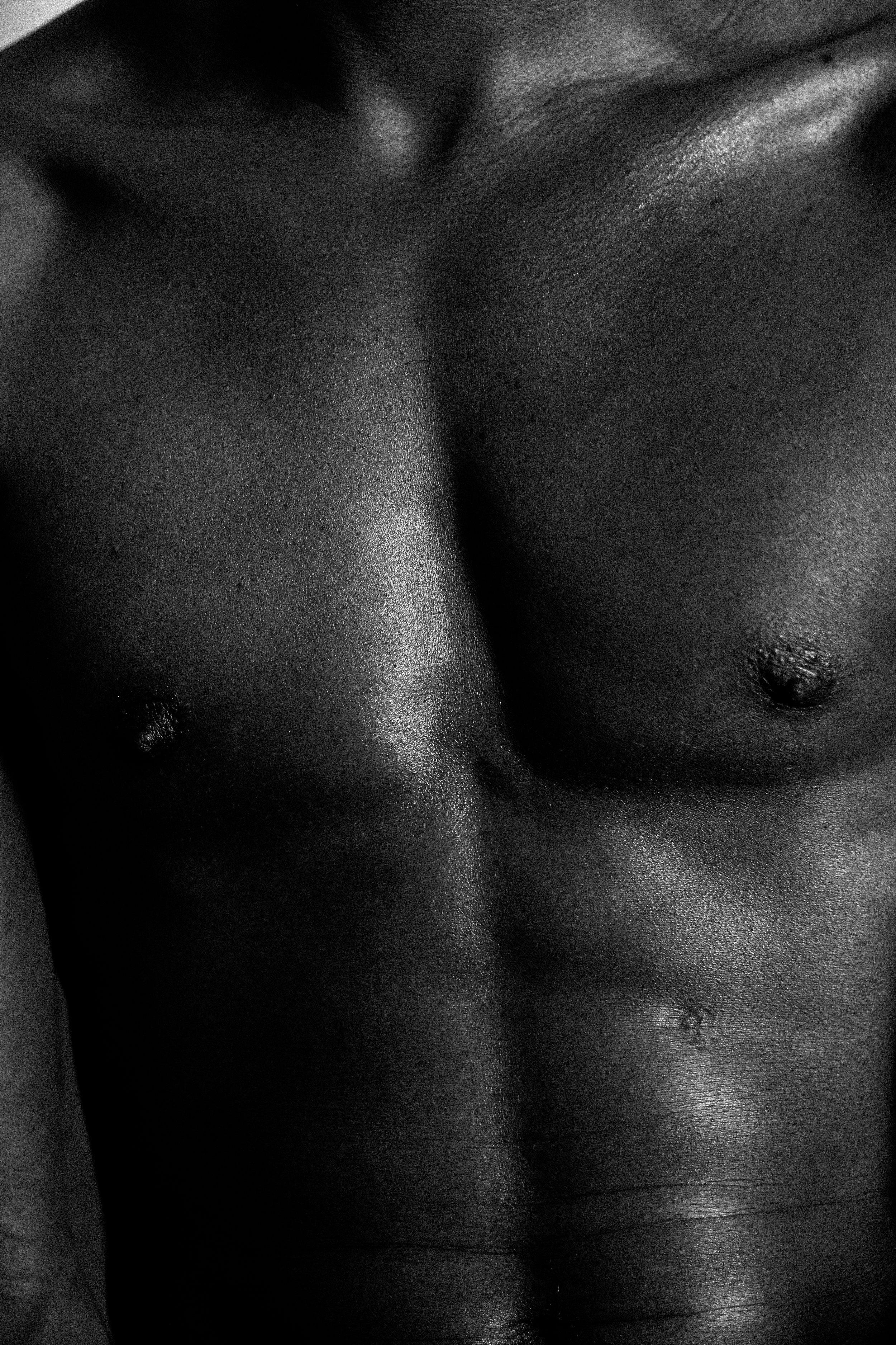 [Image Description: A black and white close up of a black man's chest deep in shadow, a scar is partway down his left abdomen]