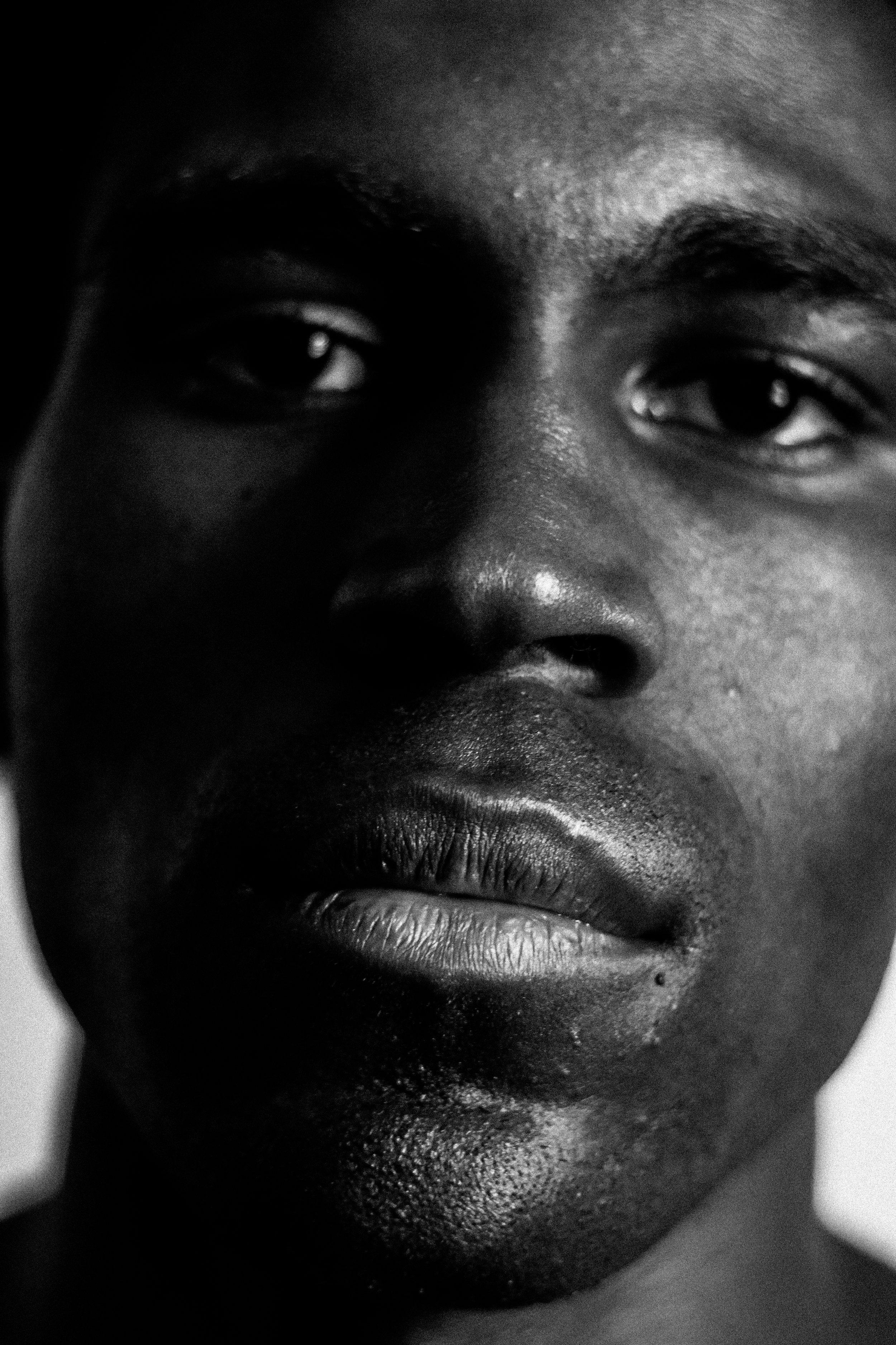 [Image Description: a black and white photograph of a black man's face, he stares straight ahead into the camera mouth closed]