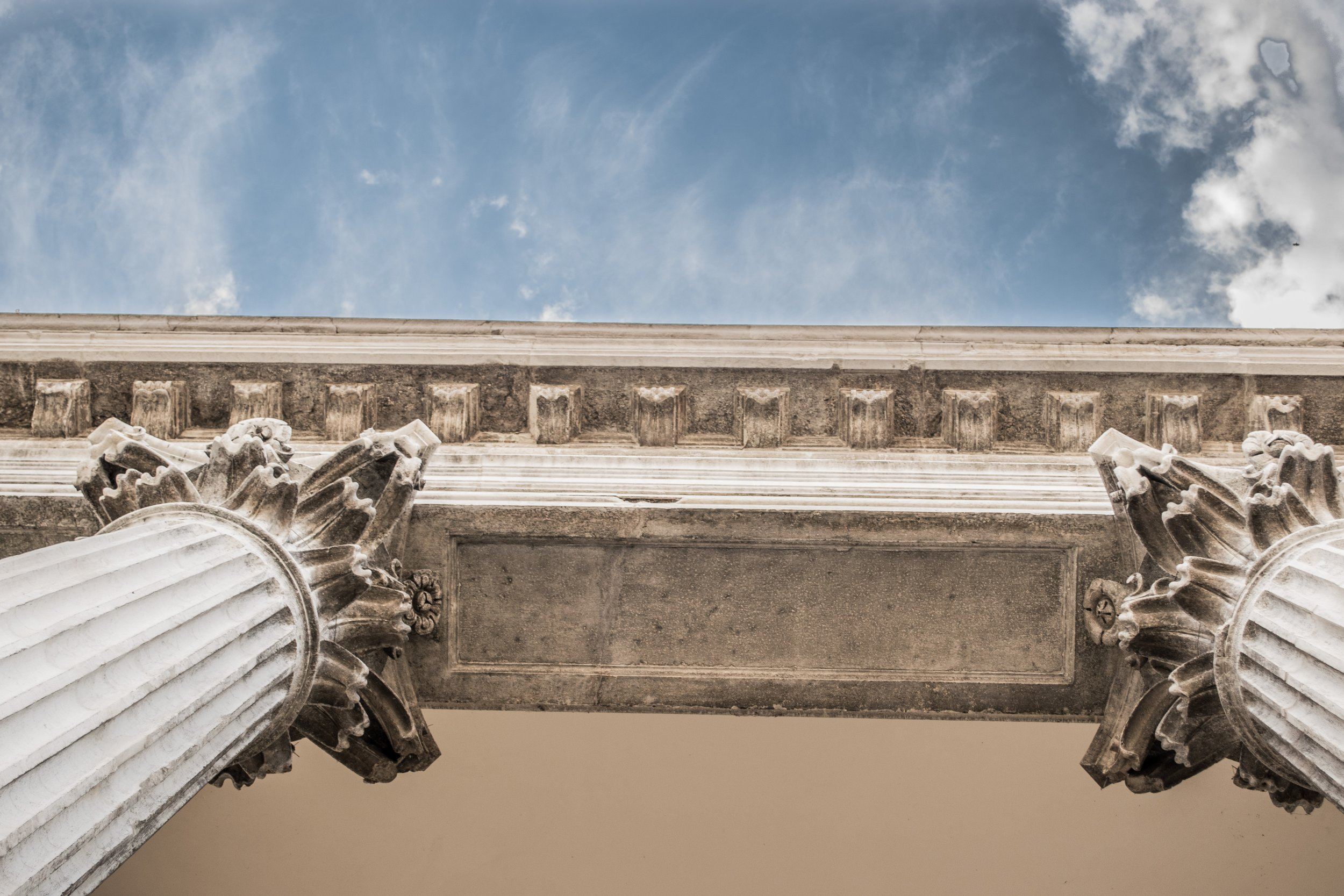 Photo by  Inma Ibáñez  on  Unsplash     [Image Description: Blue sky and fluffy white clouds float above a worm's eye view of two white neoclassical pillars.]