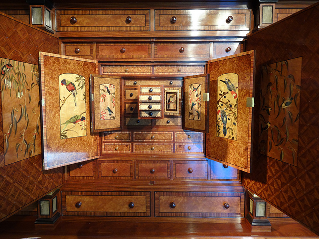 [Image description: photograph of an intricately crafted chest of drawers with cupboard doors wide open to reveal colourful inlaid birds.]  denisbin / Creative Commons
