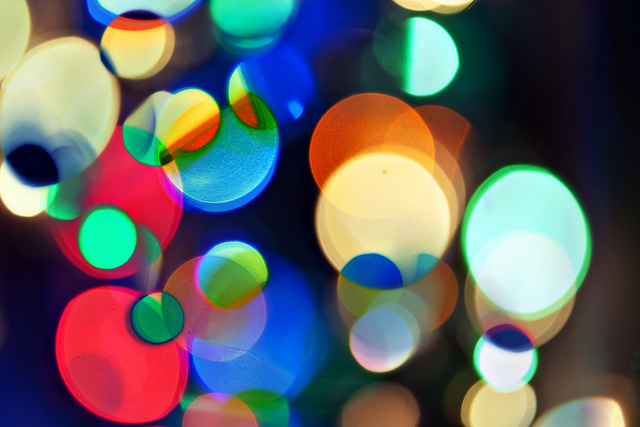 [Image description: close photograph of sequins inside a kaleidoscope; overlapping circles of blurry, brightly-coloured light.]  ok, shawna / Creative Commons