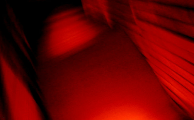 [Image description: blurry photograph of a wooden staircase. The entire image is toned red.]  Nico Paix / Creative Commons