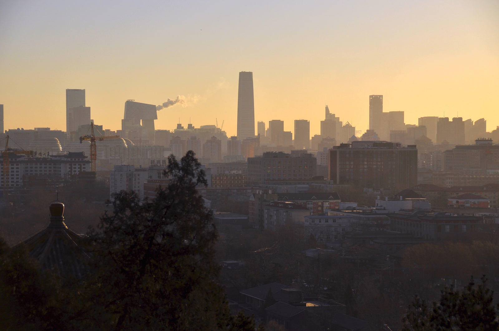 [Image description: photograph of the Beijing skyline at sunrise. The foreground is shadowy, and filled with trees and smaller traditional buildings. The background is bright, with skyscrapers and plumes of smoke.]  faungg's photos / Creative Commons