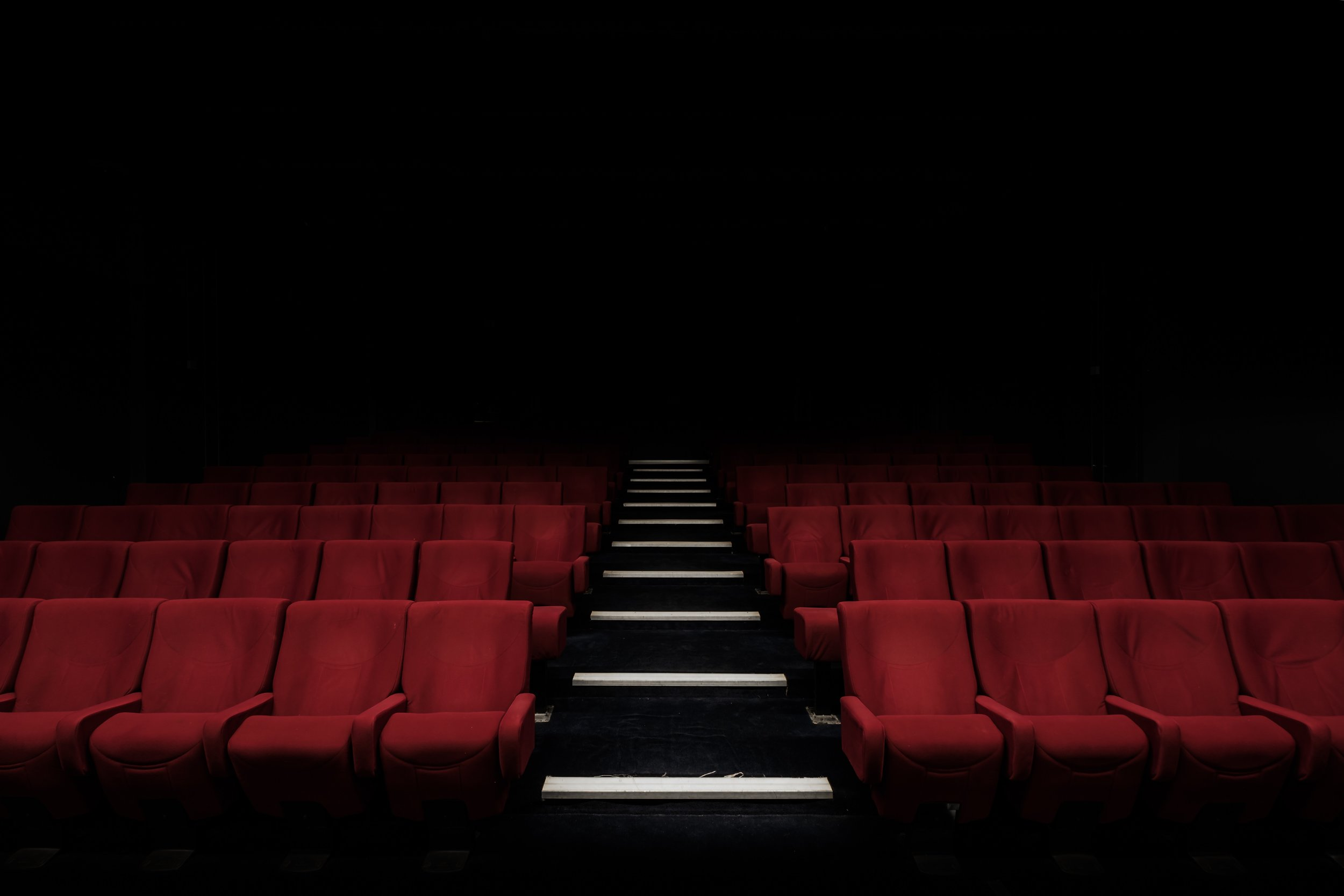 Photo by  Felix Mooneeram  on  Unsplash    [Image Description: A darkened theatre with empty rows of red seats with an aisle running through the centre.]