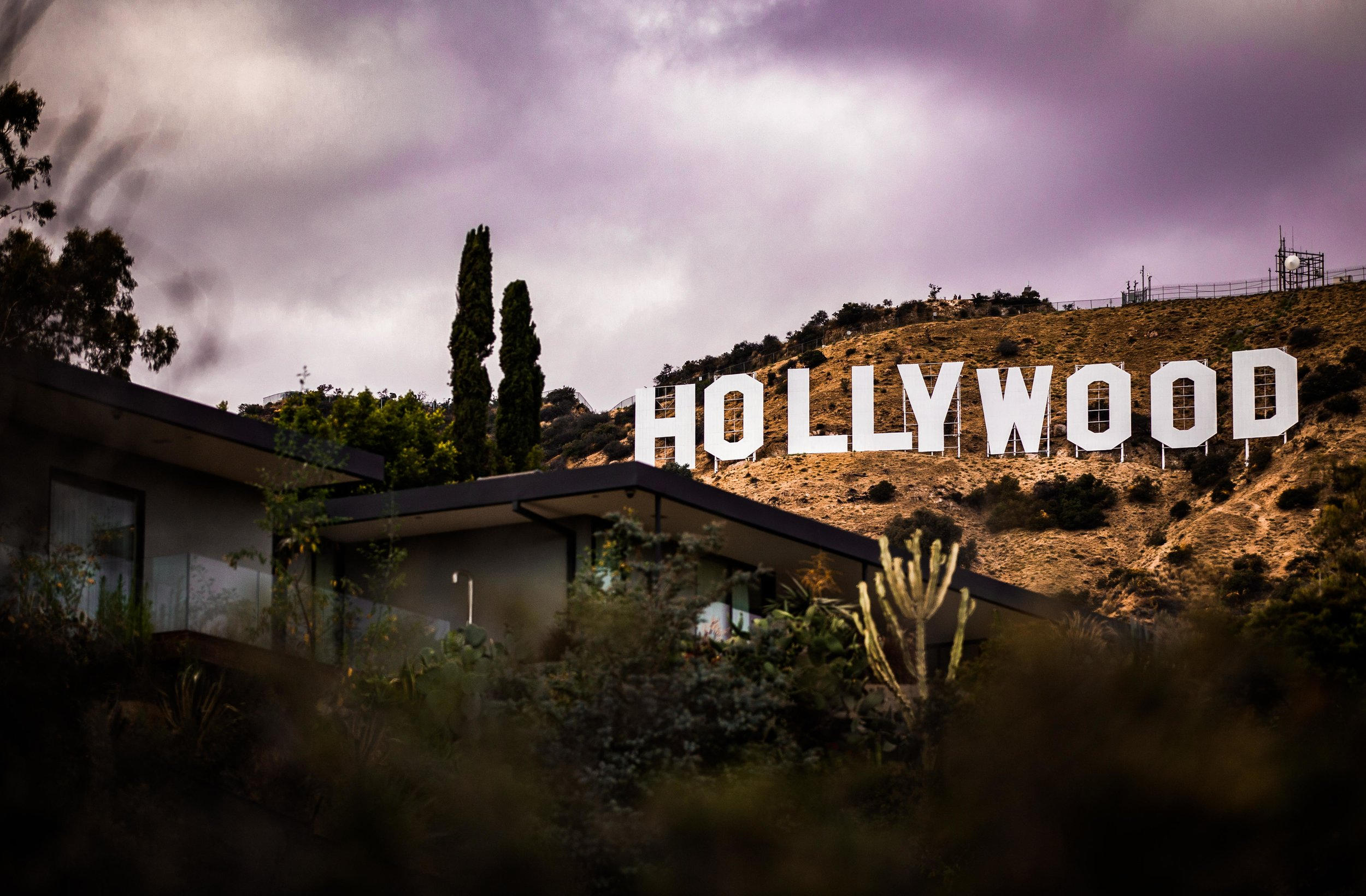 Photo by  Martin Jernberg  on  Unsplash    [Image Description: A modernist house sits on the Hollywood Hills with the Hollywood signs against a muted lavender sky in background.]