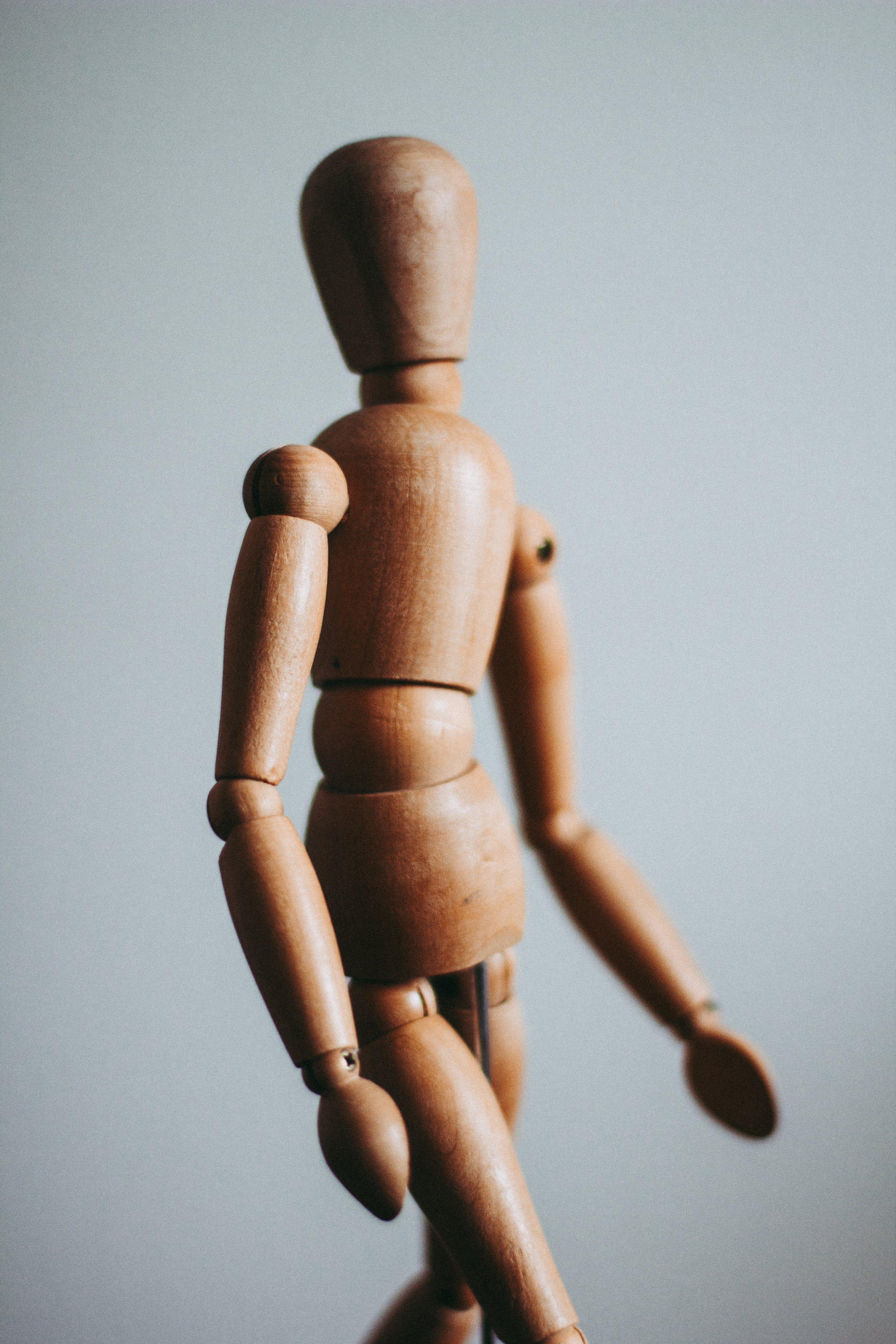 Photo by  Kira auf der Heide  on  Unsplash    [Image Description: A wooden, articulated figure doll stands against a grey background]