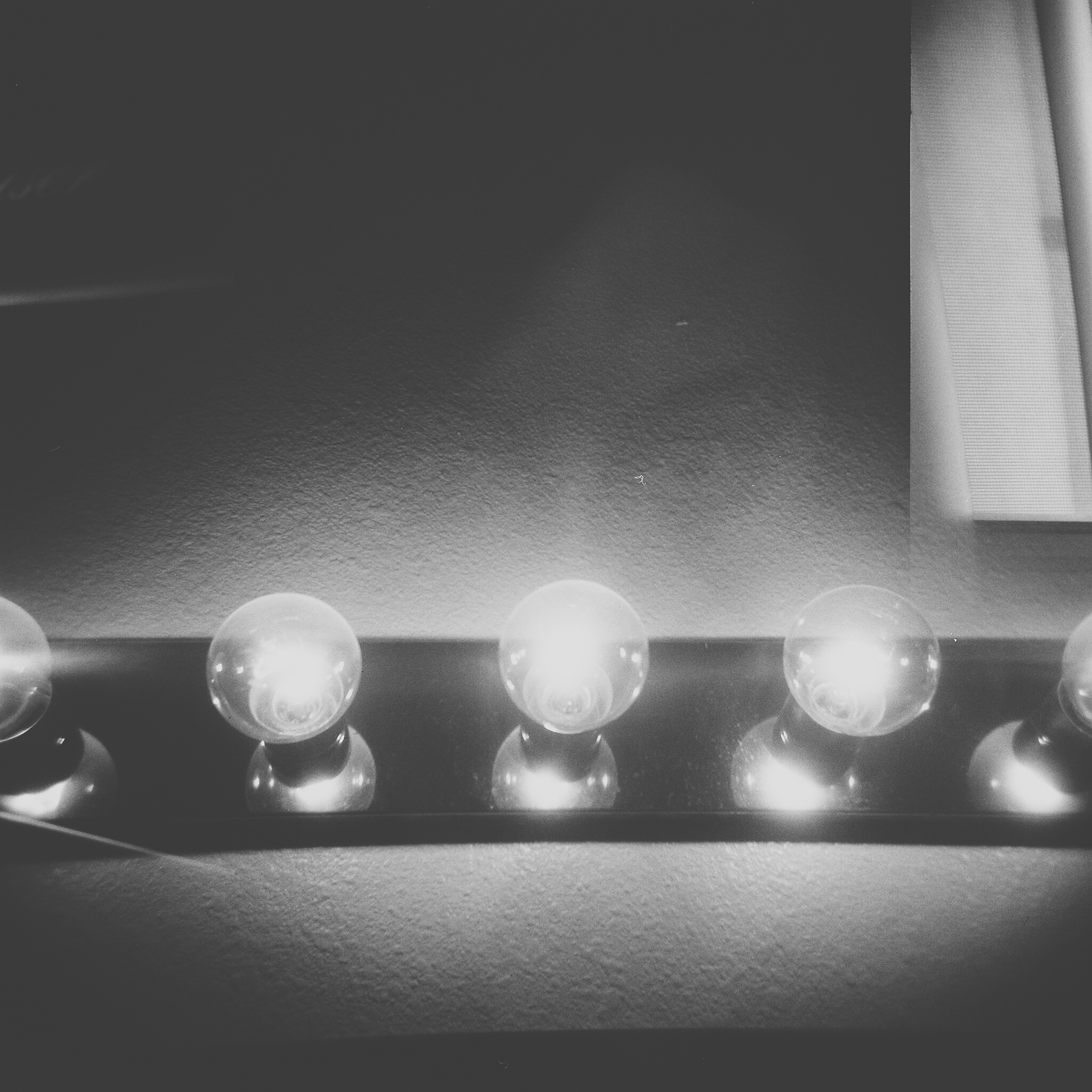[Image description: black and white photograph of a row of vanity bulbs. There is a very faint image of a face looking straight at the camera layered over the shot, like a weak double exposure.]  Holly Lay / Creative Commons
