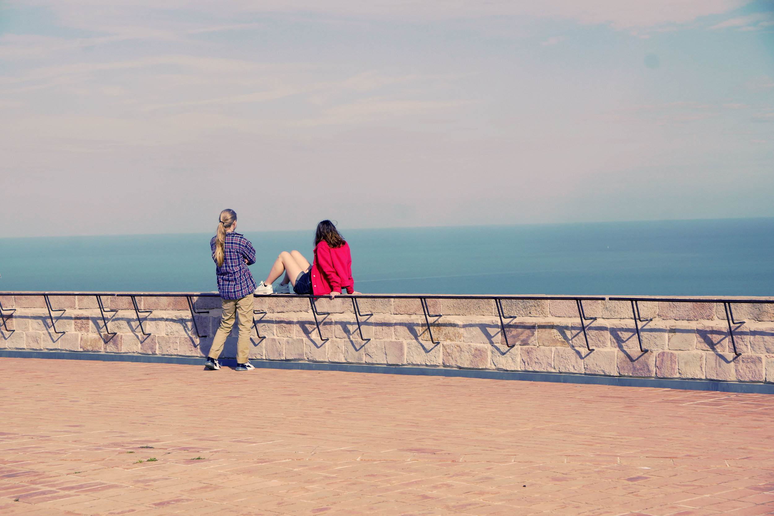 Soph Bonde/Argot Publications Inc   [Image Description: Two people over look a ocean vista, they both have long hair, the one to the left sits on a stone wall and stares out over the water, the person to the right has their arms crossed over their chest]