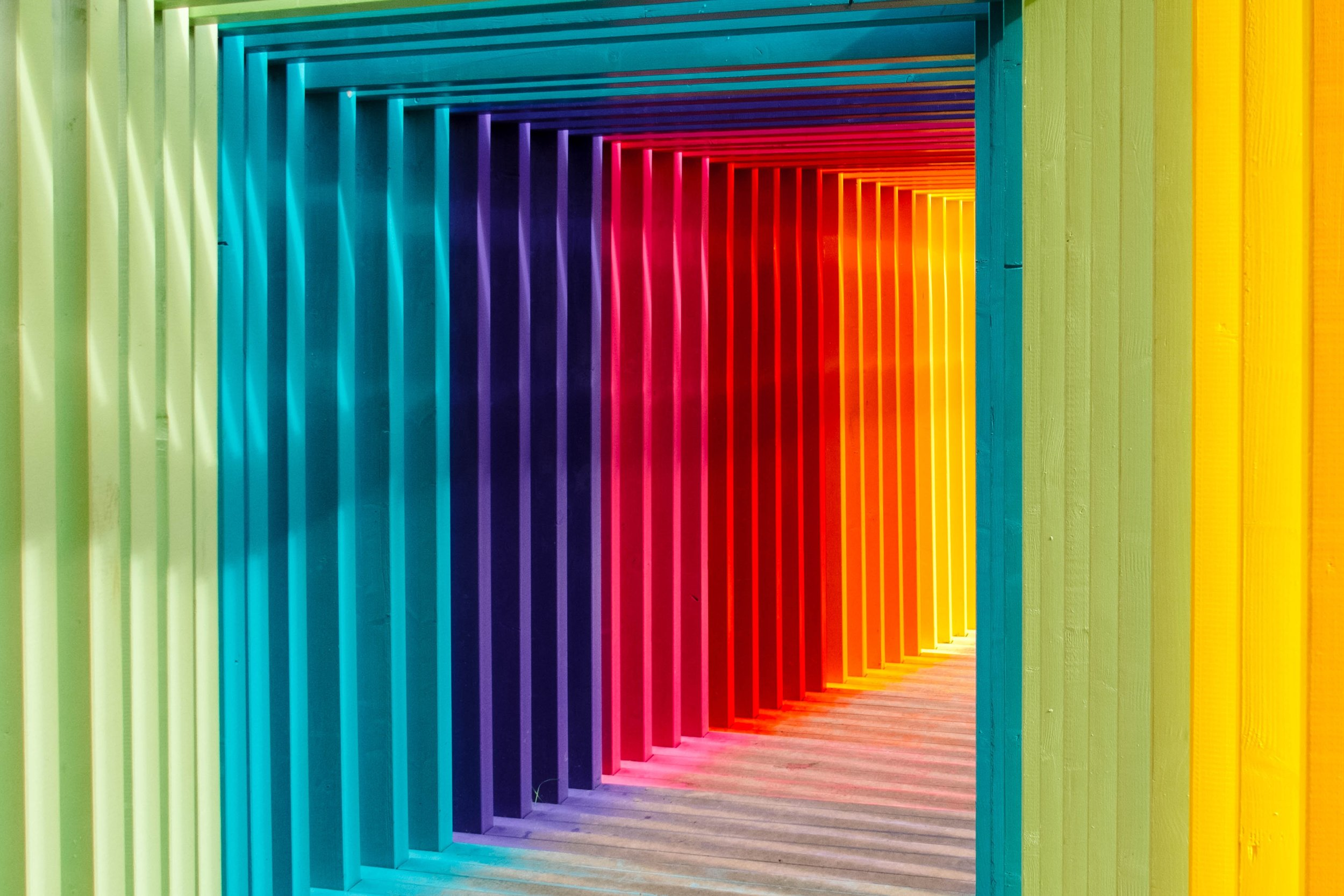 Photo by  Robert Katzki  on  Unsplash    [Image Description: Sunlight filters through square archways in green, teal, purple, red, orange and yellow.]