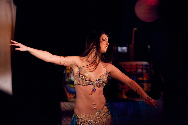 Photo via  Flickr    [Image Description: A spotlight shines on a belly dancer in a gold two piece ensemble has their arms outstretched against a darkened background]