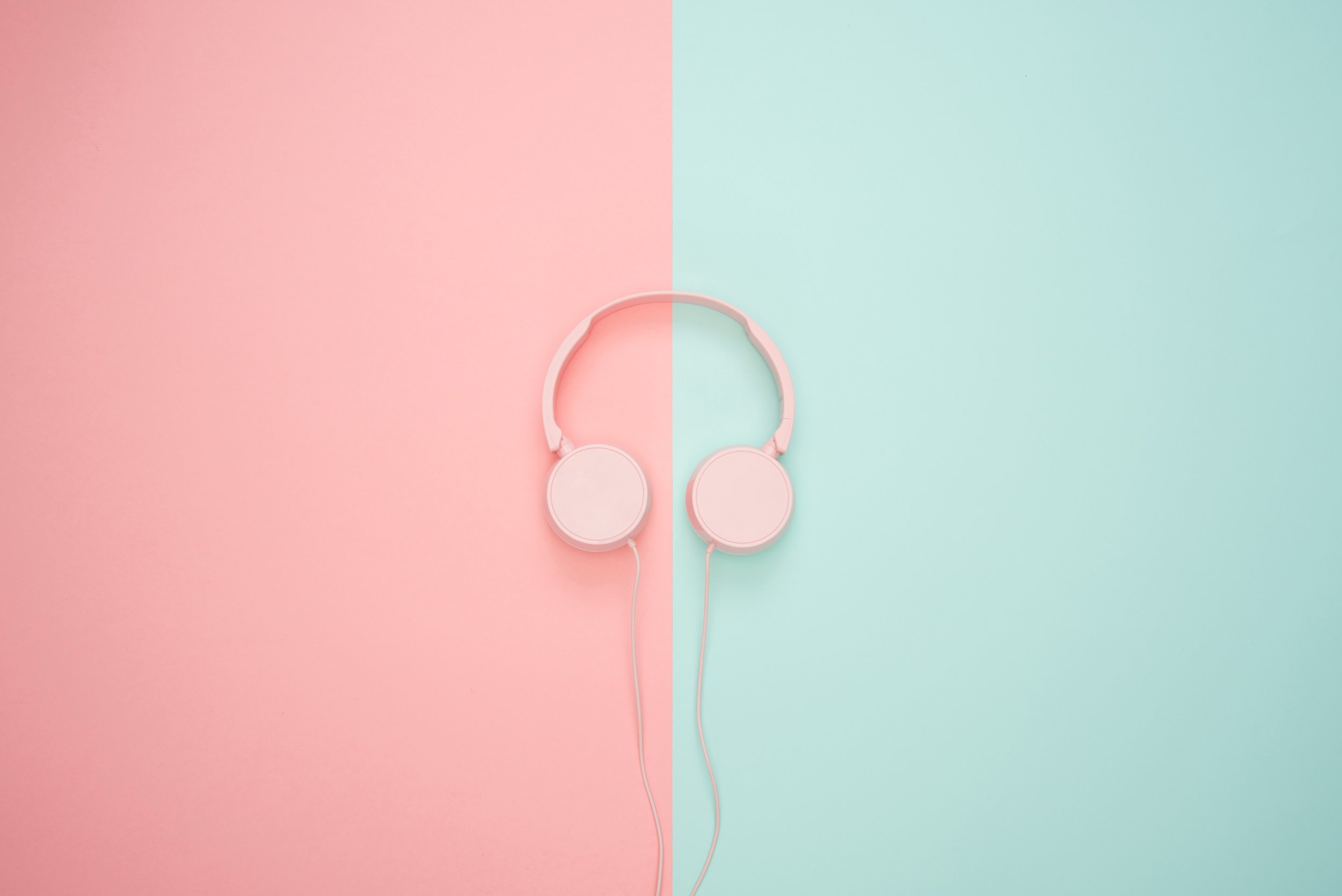 Photo by  Icons8 team  on  Unsplash    [Image Description: Pink headphones lay flat on a pastel pink and mint background]