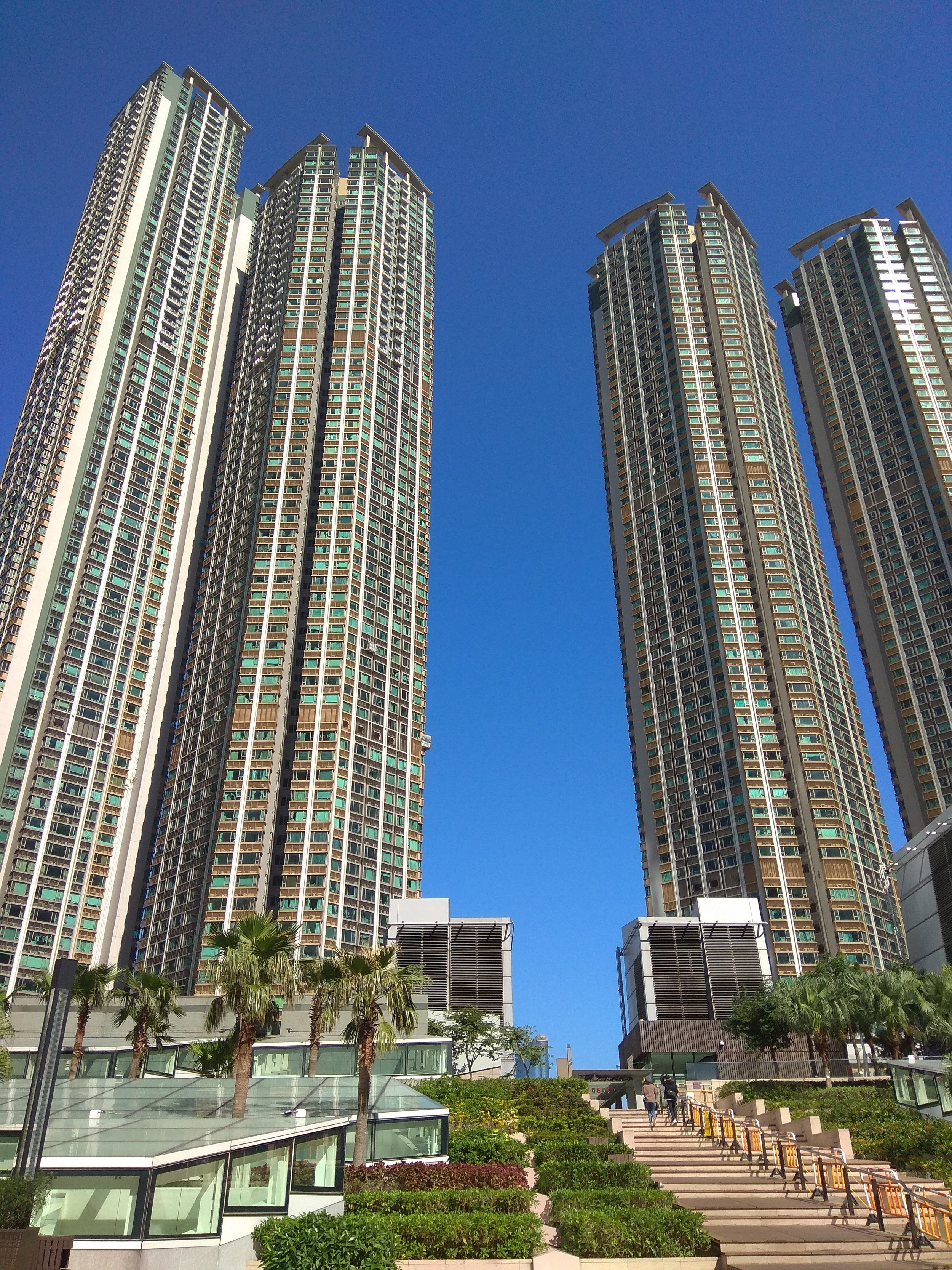 [Image description: photograph of three huge skyscraper buildings in bright sunlight against the background of a deep blue sky.]  Photo credit to the author