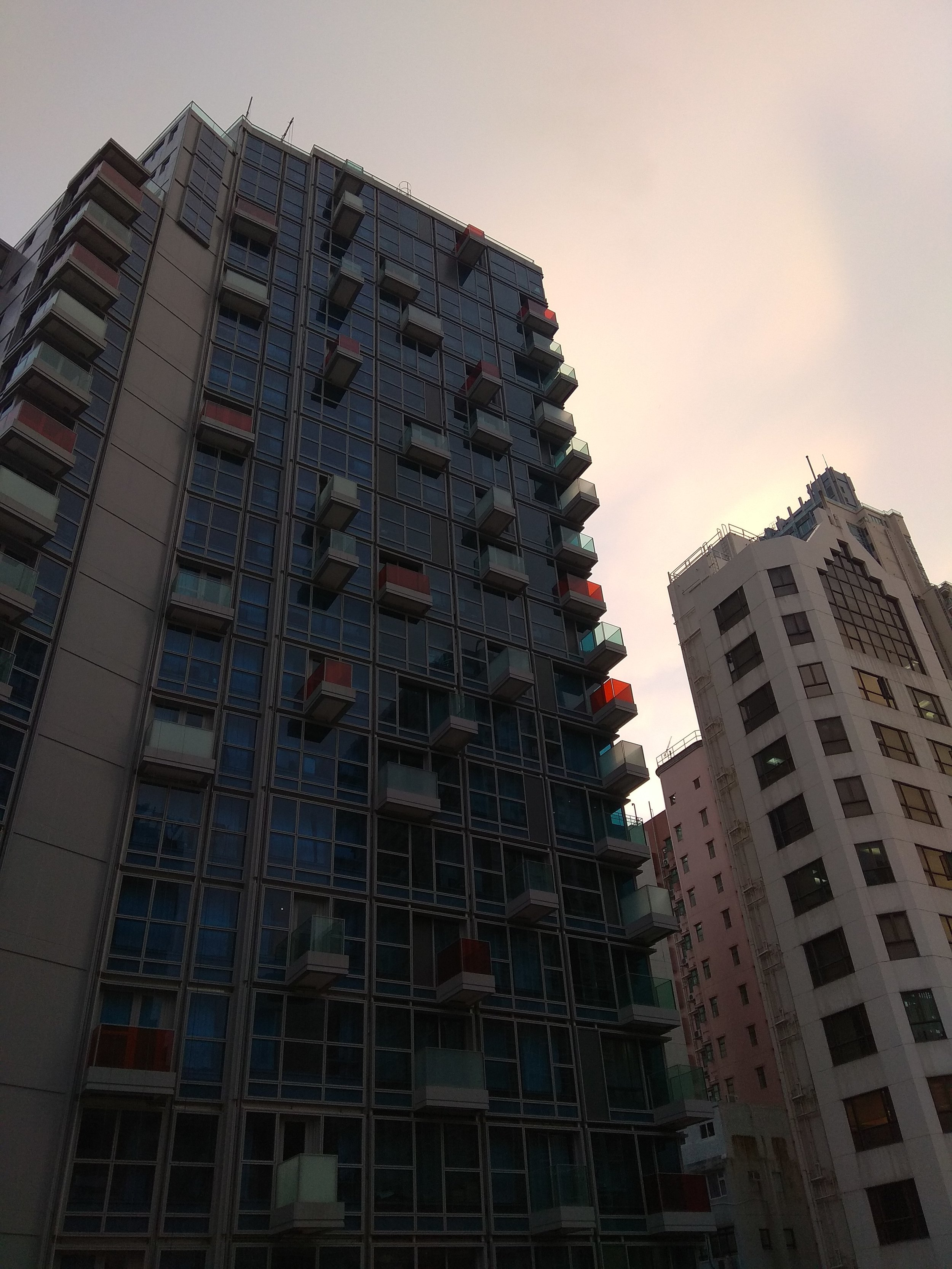 [Image description: photograph of a Hong Kong high-rise building with a dark glass façade and balconies of different colours at seemingly random intervals. There is a smaller, pale high-rise building to the right of the larger one. Late evening sun washes the sky above.]  Photo credit to the author