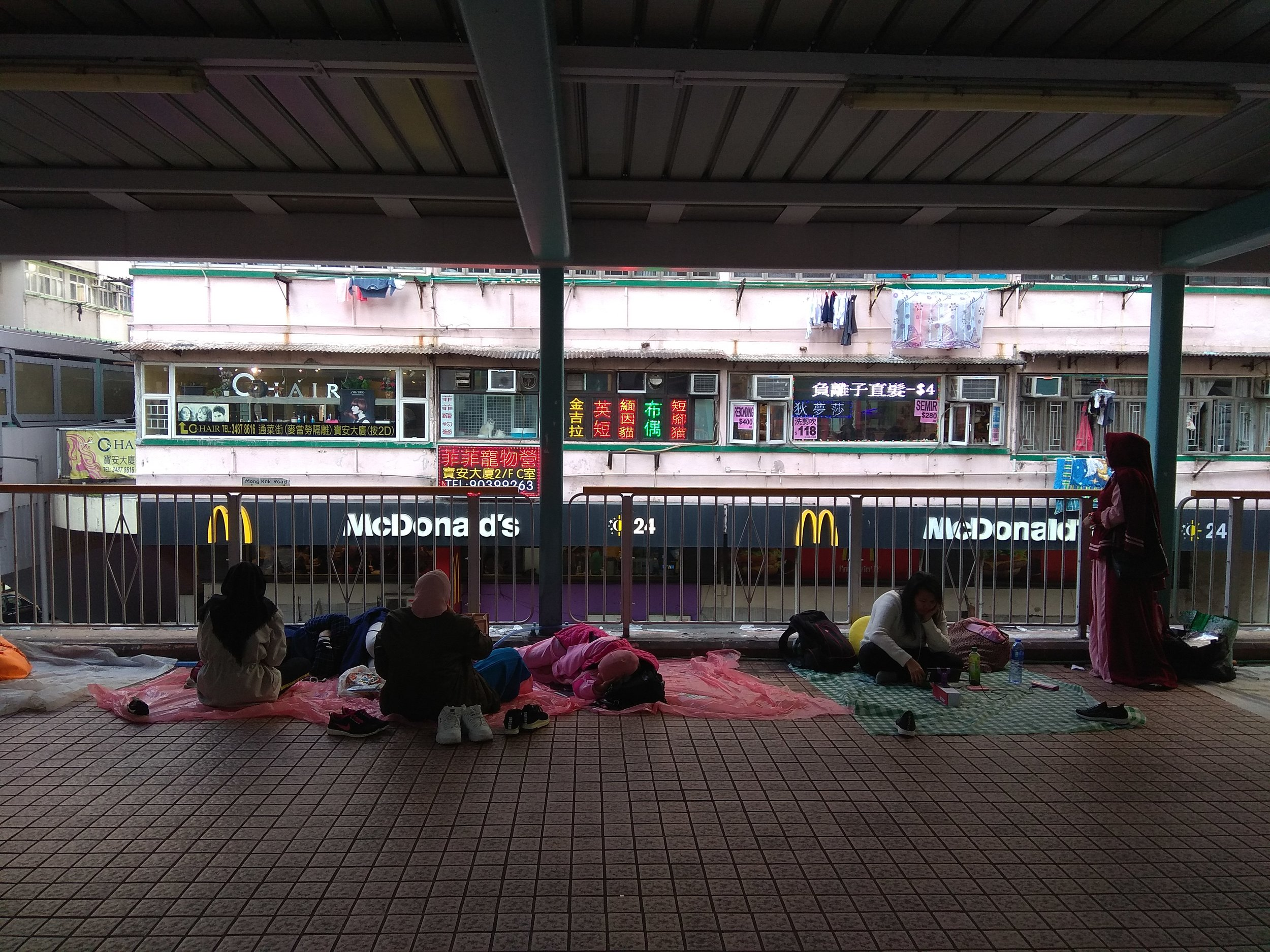 [Image description: photograph of people resting on blankets and tarpaulins in a public walkway. The foreground where they sit is dimly lit, and the background of shops and restaurants is bathed in brighter light.]  Photo credit to the author