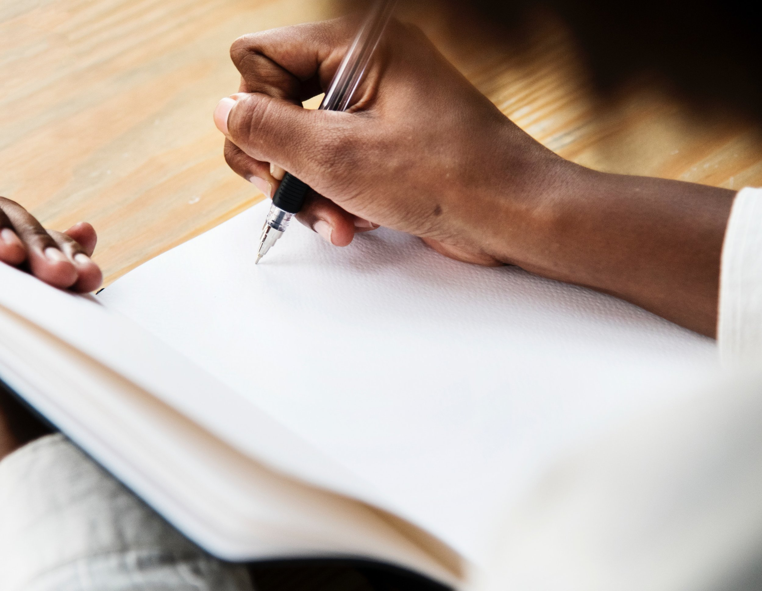 Photo by   rawpixel.com   from   Pexels     (Image Description:     Zoom up of a dark skinned person holding a notebook, hovering pen over a blank page}