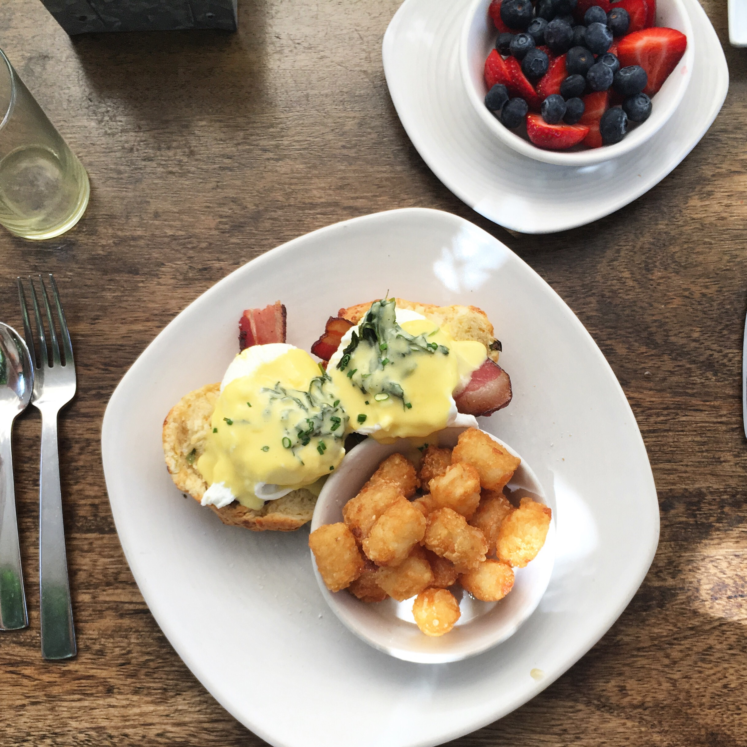 Cheekys Eggs Benedict with herbed hollandaise on a homemade scone, complimented by jalapeño tater tots