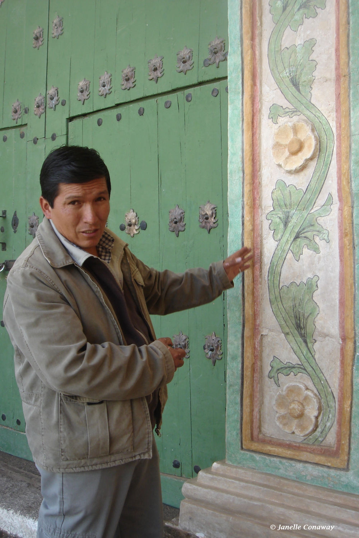 Restorer Juan Carlos Cavero Catalán points out design details at the entrance to the Lari church.