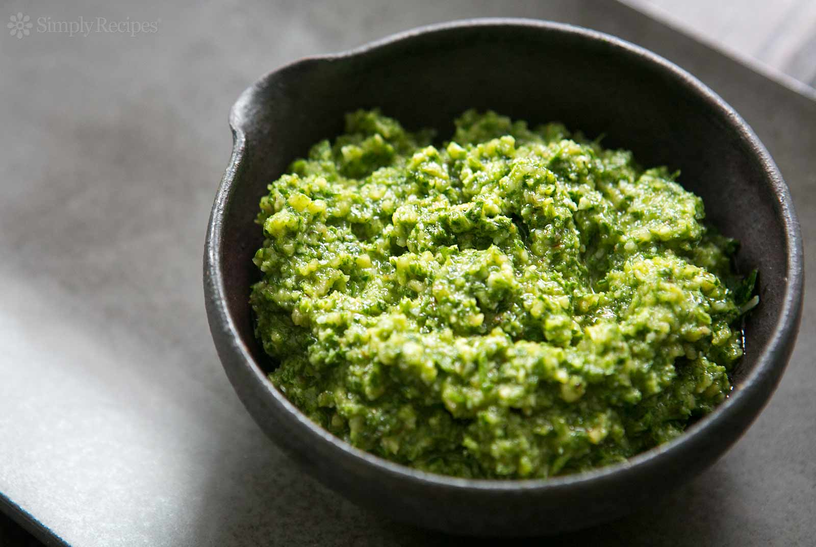 """Easy and Durable Basil-Walnut Pesto   Place one cup of walnuts, 1 minced garlic clove and 1/2 teaspoon of sea salt in your food processor and grind till nuts are grainy. Add three cups of fresh basil leaves (till it fills your container), drizzle 1/4 to 1/2 cup of finest quality olive oil over the top, then grind till you have a serviceable, coarse paste. (I often make extra to store in zip-lock plastic bags that I flatten into """"bricks"""" and stack in my freezer. Keeps for months without losing flavor.)"""