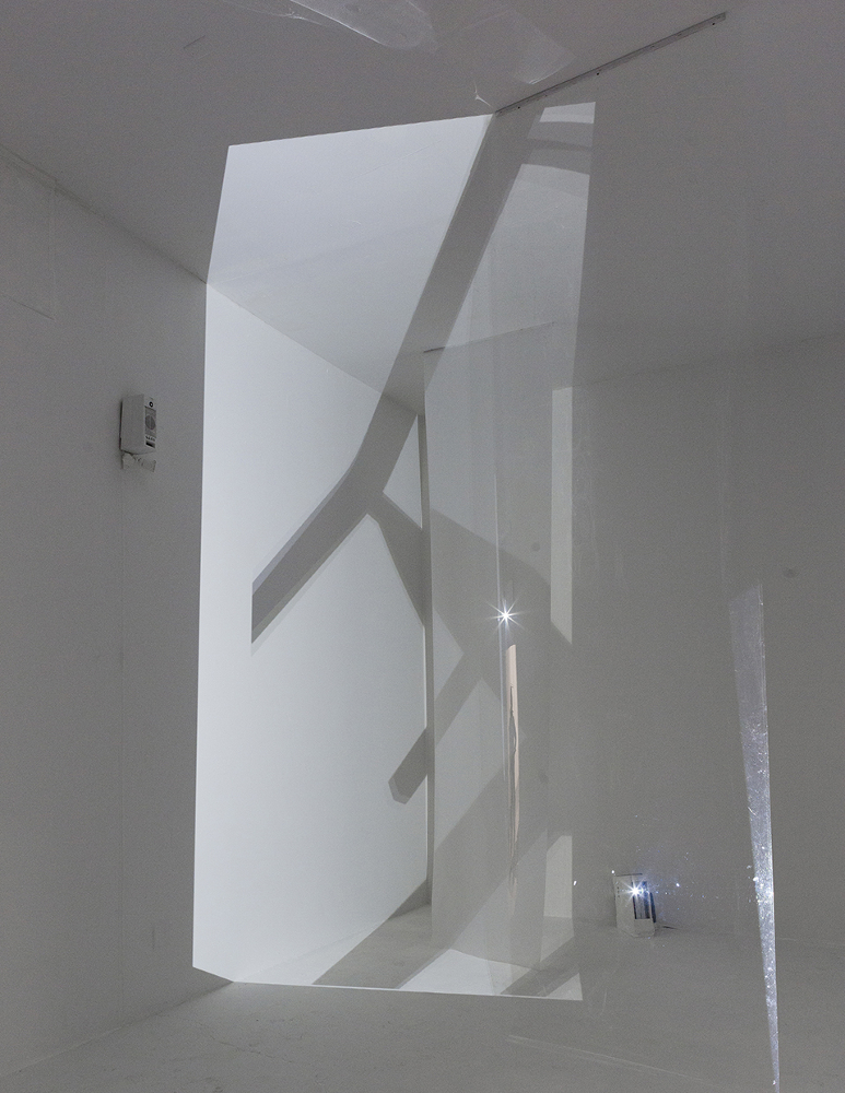 The second room is white, with floor to ceiling screens: two architectural vellum and one acetate film. Shades of white, corners and walls blend. The space, fractured by projection spills and refractions of luminous media, constantly shifts the horizon line. Four channel audio tracks of scissors clipping matter sonically interpenetrate the space.