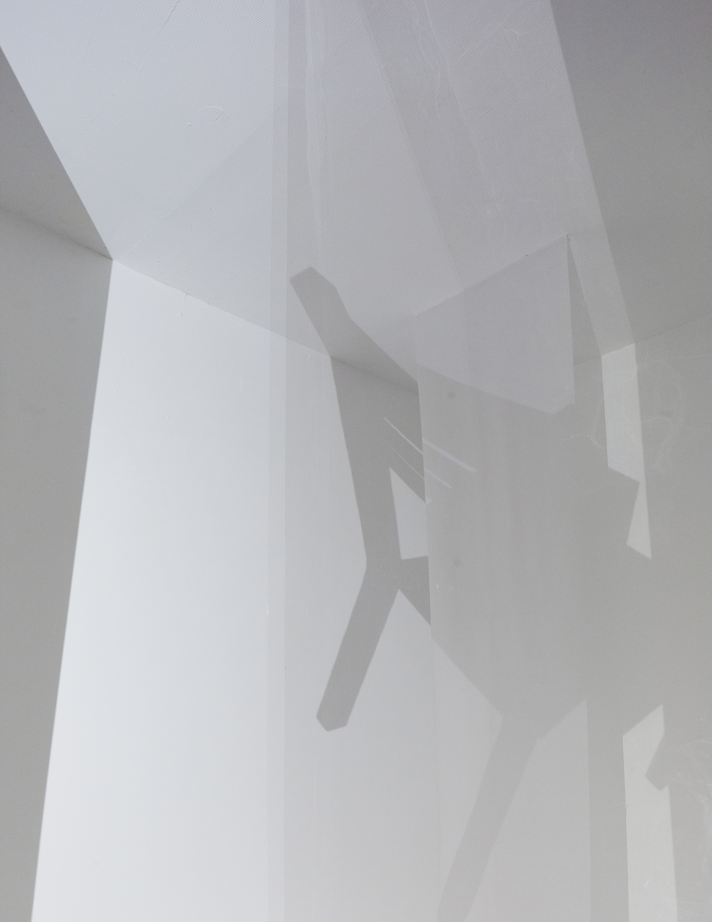 """The animation of a shadow of the chair thrown into space traverses the space on an infinite loop, crossing from one corner through the viewer and to the opposite corner. The chair passes through states of dimensionality: shadow on the screens, getting closer to the center of the room, disappearing when it """"flies"""" through the room therefore existing only in the viewer's mind and reappearing on the opposite side of the room only to diminish and fly off into the void."""