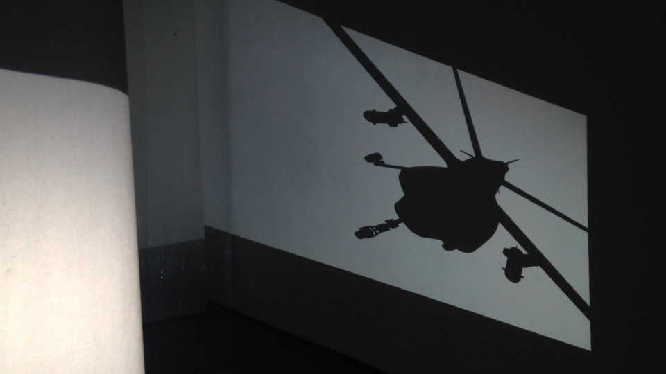 The projections are 3D animations of a predator drone. The drone appears to fly toward the center of the space from one wall and come out, leaving the opposite wall, flying into distance.