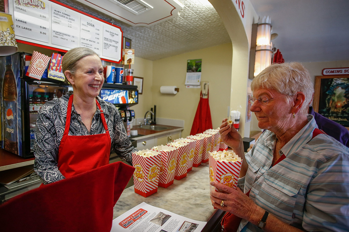 Caryn Hansen Georgen (L)   Ruby Theatre   supervisor,  serves up some delicious popcorn.