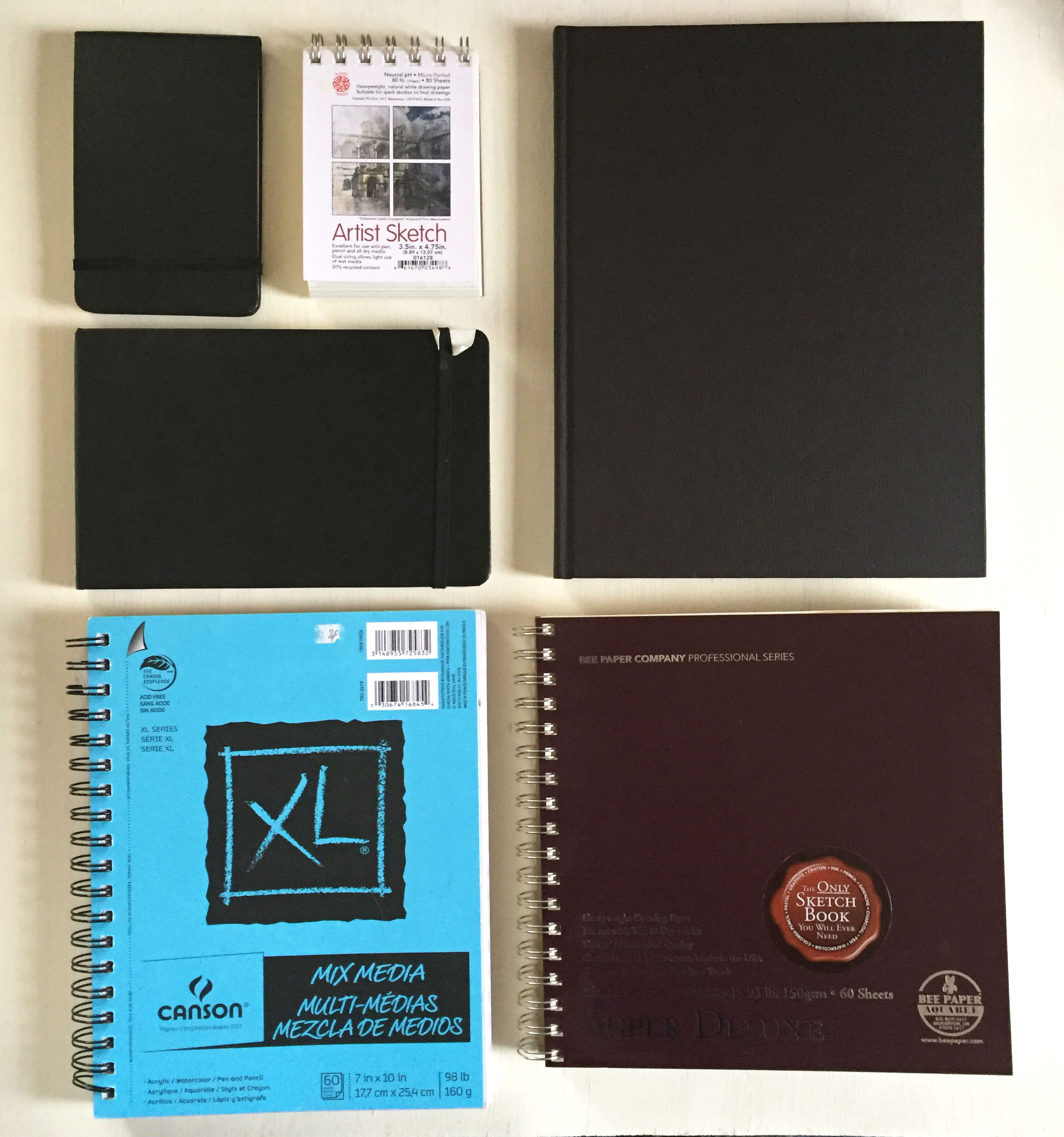 My current sketchbook collection (Clockwise from top left): Moleskine Watercolor Notebooks (black rectangular), Pentalic Pocket Sketchpad, Strathmore 500 Series Mixed Media Art Journal, Bee Paper Aquabee Super Deluxe Sketchbook, Canson XL Mixed Media Pad