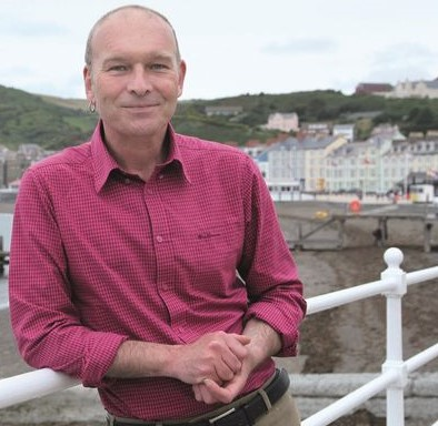"""Mike Parker's writing always begins from a sense of place, Wales in particular. That has sparked various narrative non-fiction books, including  Map Addict, The Wild Rover  and  Real Powys , TV and radio programmes and some one-man stand-up shows. Politics is always there too. after failing to become the Plaid Cymru MP for Ceredigion in 2015, wrote  The Greasy Poll  about the """"drumbeat rise of neo-fascism"""" that I'd found on the campaign trail. That was before Brexit, before Trump: the signs were all there.  His new book,  On the Red Hill , to be published in June 2019 by William Heinemann, is a celebration of the queer rural, love, acceptance, finding home and the redemptive power of nature, and all in the hills around Machynlleth."""