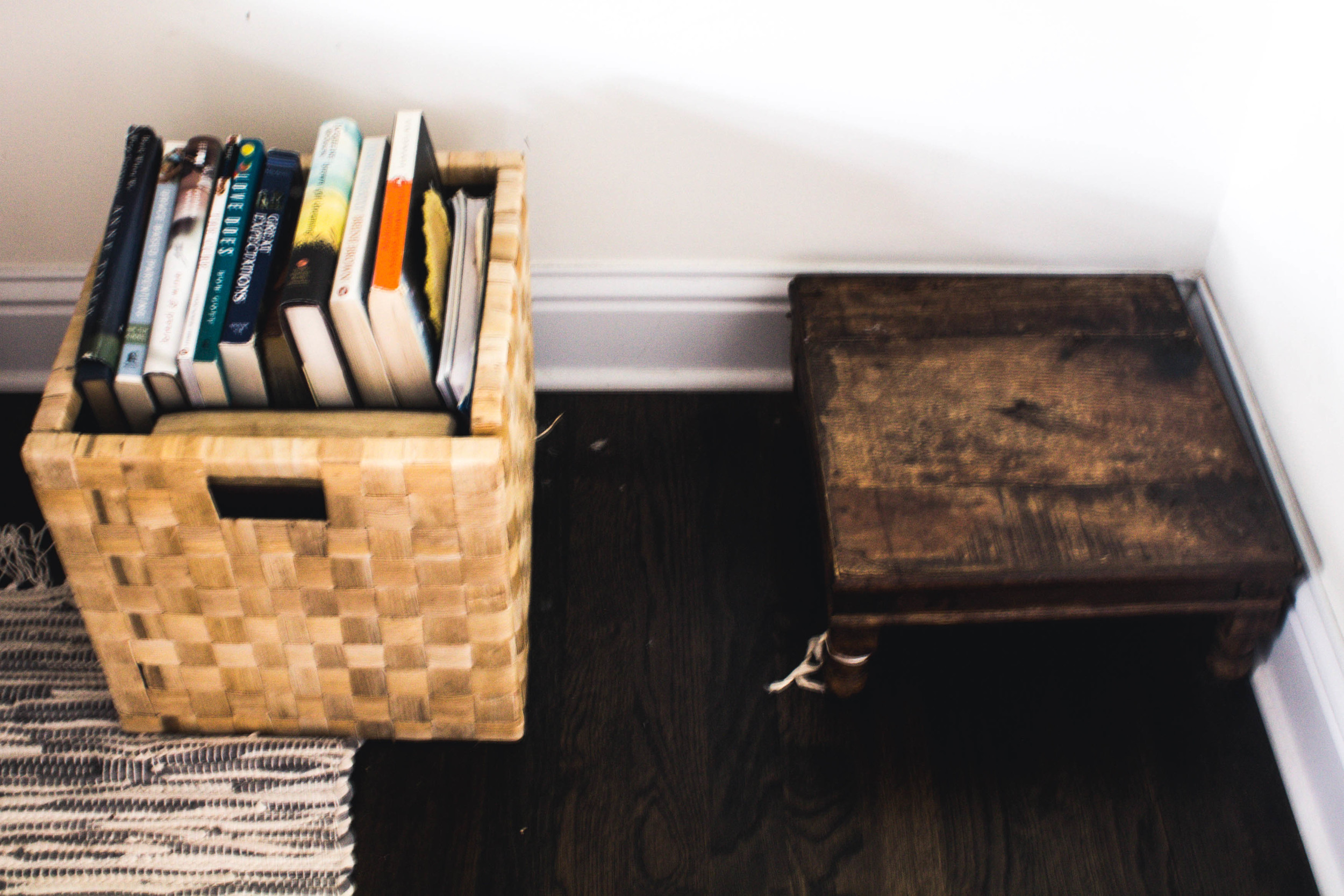 A simple basket holds just a fraction of all the books to be found throughout the house, partnered with a low wooden pedestal that compliments the hardwood flooring.
