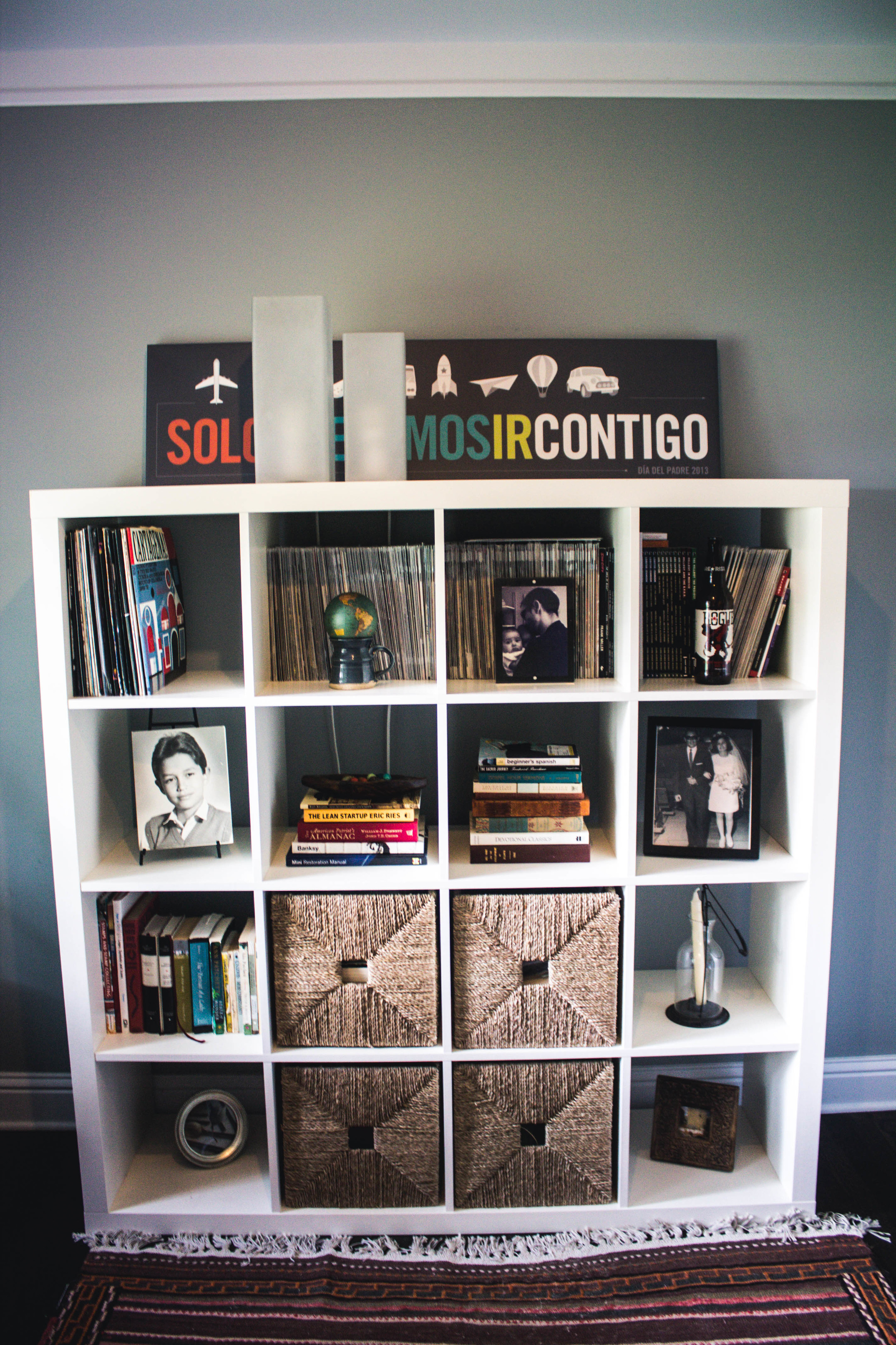 """The bookshelf in the office houses books, memorabilia, family photos, and treasured gifts. The sign on top says in Spanish, """"We just want to go with you."""" It was a Father's Day present to Mauricio, an homage to his love of travel and transportation. The rug was a gift from Nancy's father and was made in Iran."""