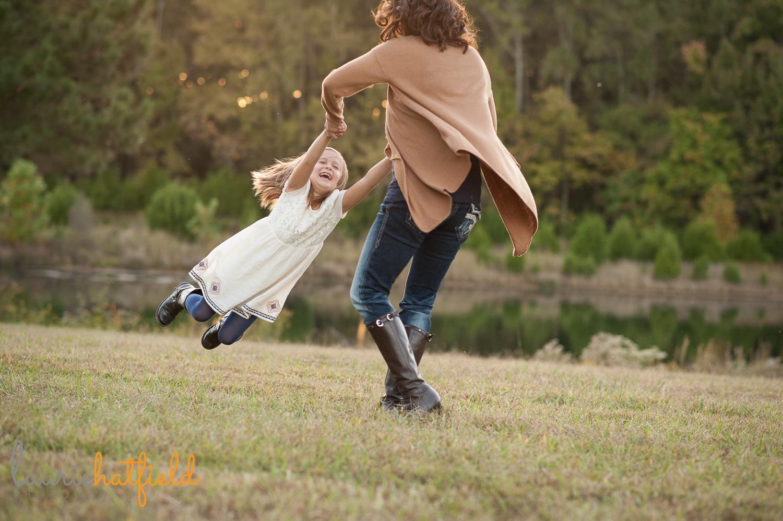 Mom swinging daughter picture