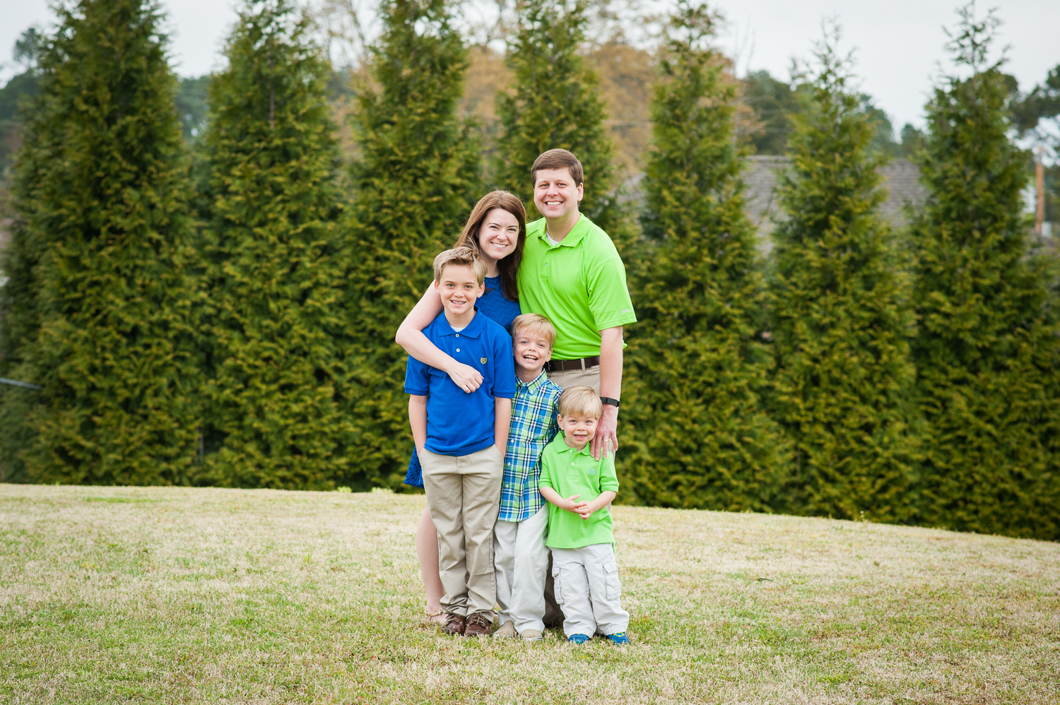 mom, dad, and 3 sons standing in grass   Huntsville photographer