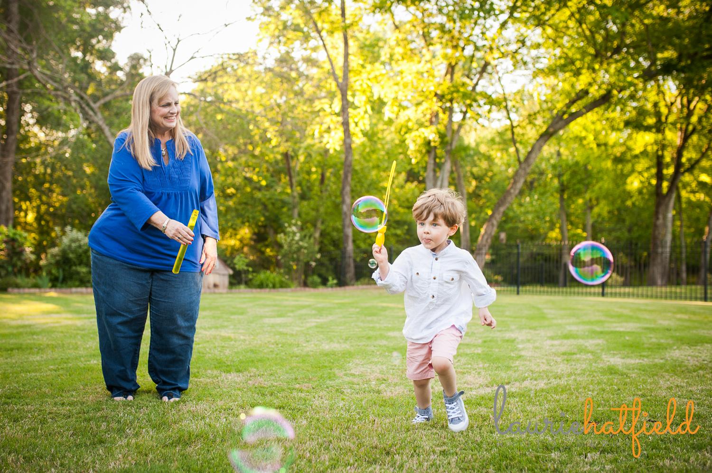 grandparents blowing bubbles with grandson | Huntsville mini sessions