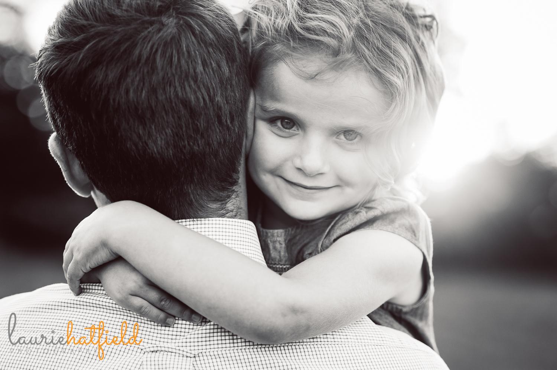 girl peeking over dad's shoulder | Huntsville child photographer