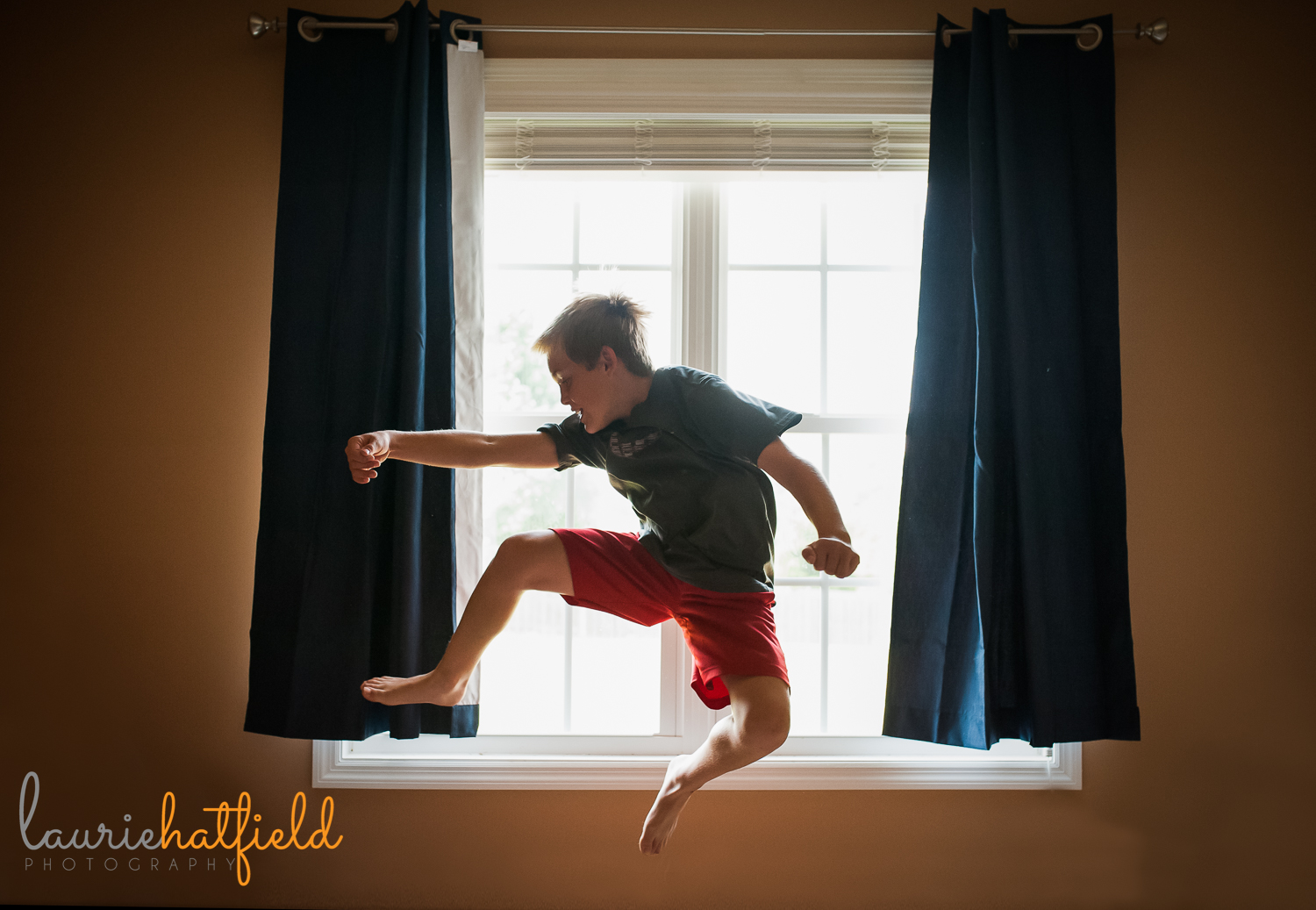 boy jumping in front of window   Huntsville child photographer