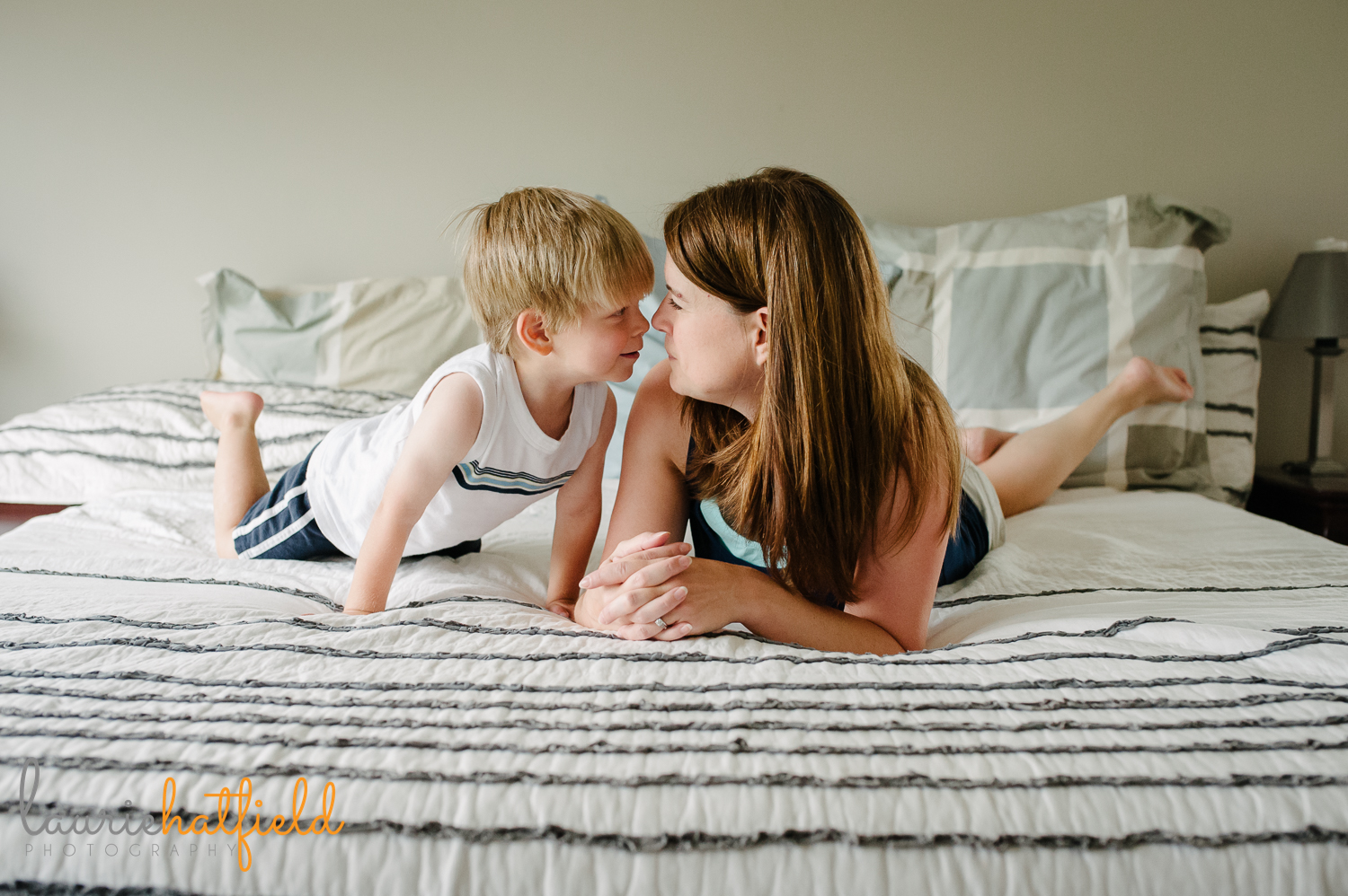 mom and son touching noses on bed | Huntsville family photographer